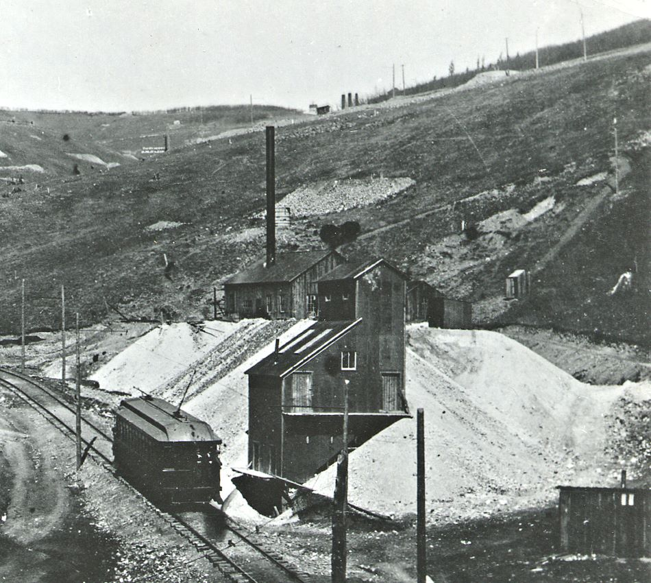 "Cripple Creek District Railway Trolley seen passing the ore house of the Chicago Tunnel in Poverty Gulch, taken no later than summer of 1899. This due to this picture appeared in ""The Engineering Magazine"" for September 1899.    This section of track in Poverty Gulch was built in 1897 (between April and December). Track abandoned 1903, grade here is 7.5%!!"