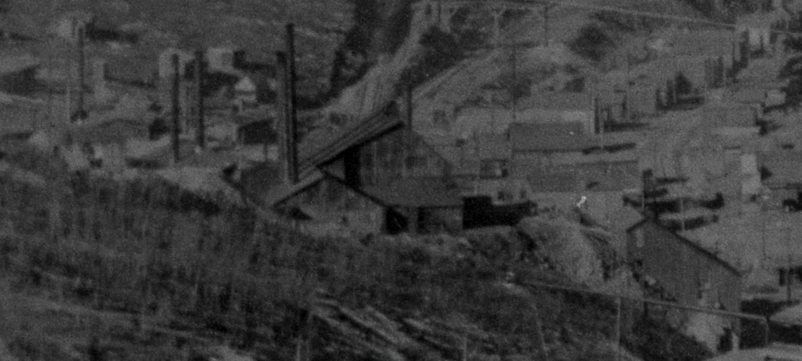 View is a negative type of Photo taken by a camera of an older type of Photograph, with not the best quality film so it is rather grainy sadly. Cropped from a view of the Trolley car named Grace climbing Gold Hill high above Poverty Gulch, along the original steep High Line grade, part of the roof and front trolley pole is seen in lower right-hand corner poking into the image towards left. * The Abe Lincoln is seen center with its Shaft House and Power Plant and shed all attached together, while the Ore-House is seen towards lower right-hand corner. * Poverty gulch houses is seen on the right-hand side, and the eastern leg of the M.T. Wye is seen about middle top, where also part of the spur up to the Midland Sampler is seen.