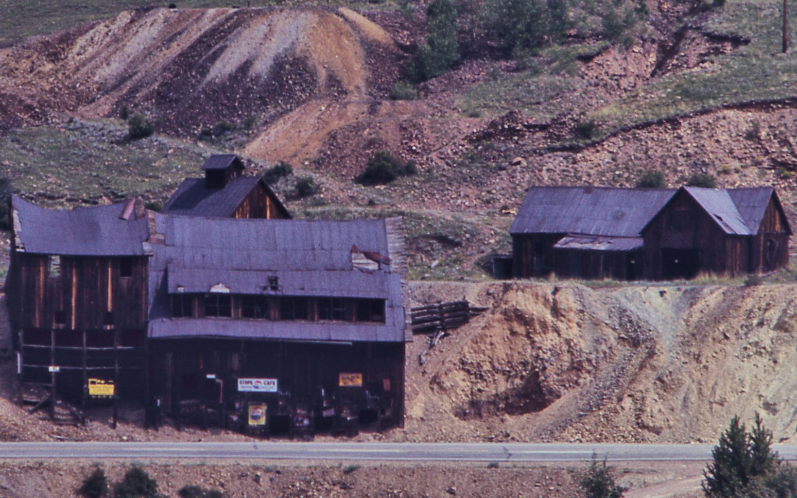 This cropped view of a slide photo from 1968 shows what is left of the Anaconda Mine structures. The Road in front of the Ore-House was the former F. & C.C. roadbed, which turned into a road when that railroad was gone, and which was later the main road between Victor and Cripple Creek towns, but today all this is gone, road and everything.    Closest to the road is the Anaconda mine Orehouse, with the Blacksmith and its cupola visible behind it, and to the right is what appears to be a tunnel opening, just left of what appears to possible be the Powerplant Structure when looking at a Sanborn 1908 Fire Insurance Map, or the Office, maybe also just be a shed like structure. Behind the structures is the former roadbed of the Midland Terminal seen, at about middle top/down, coming from left-hand side, and entering a cut behind the shed/possible powerplant structure, at the right-hand side.
