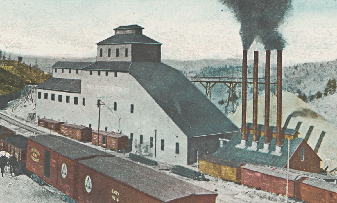 This is a cropped view of an image showing the great Mary McKinney mine in Anaconda with lot of railroad traffic in front of. It shows the business side of the mine in terms of where the coal is brought in for power the mine, and where ore is taken away. Both in and out uses boxcars, the power plant is seen at lower right, with a string of boxcars in front of it. Further on another 3 boxcars are put up to load ore from the mine plant itself, along a spur that used to be dual gauged as both the M.T and the F. & C.C. used this spur to serve this mine. After the closing of the narrow gauge this spur was used to get access down to the El Paso mine way outside the view to the left. Town of Anaconda would have been down the valley at right.