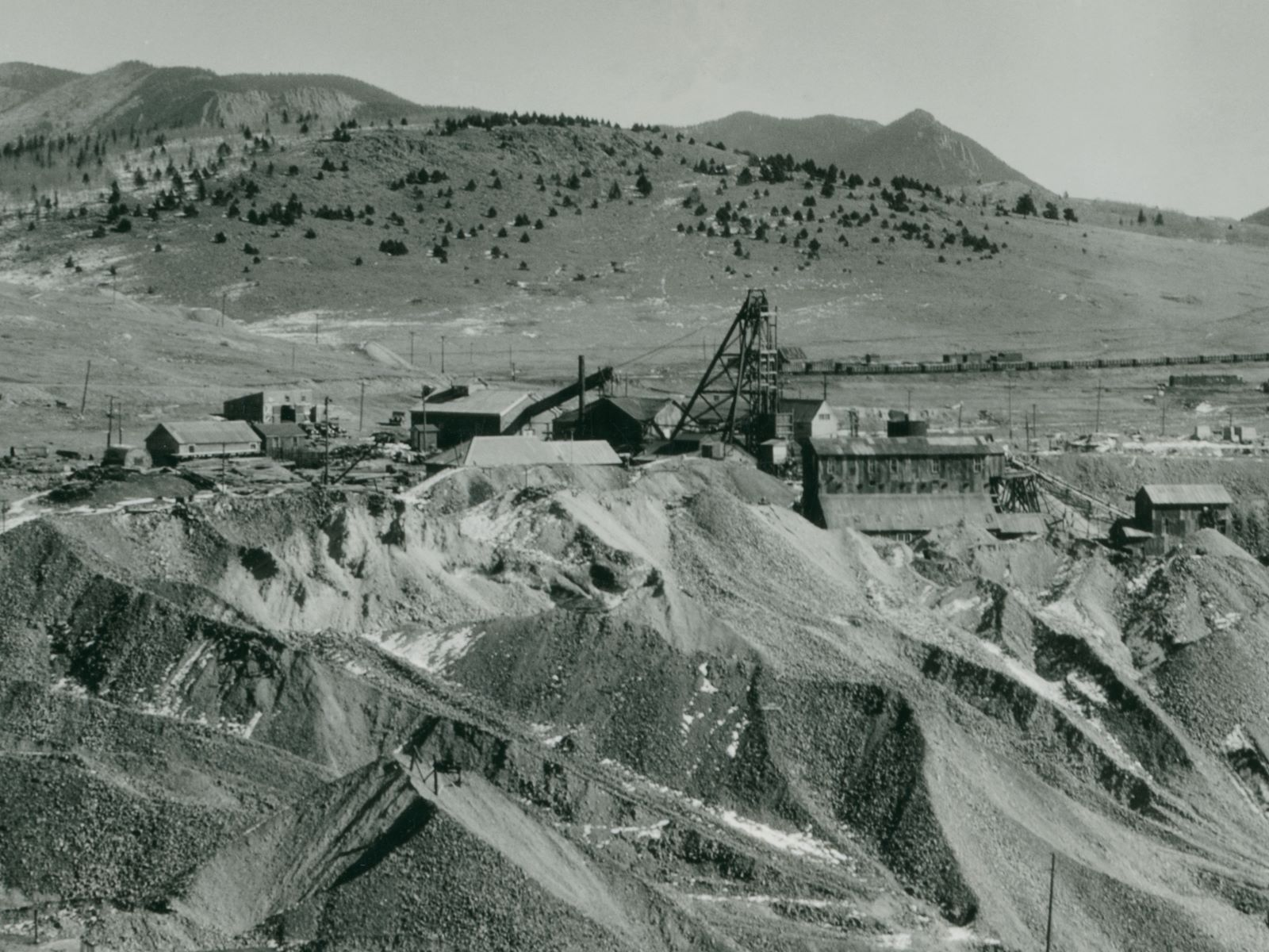Cropped view of the Vindicator Mine Operations 1934-ish style. Huge dumps covering the ground, the Ore-House is partly buried in them it appears. Not the best view, but it is a long distance shot from near the Last Dollar mine on bull Hill, so hard to get a good quality shot.    Behind the large Headframe is seen a huge string of boxcars in the Bull Hill Yards of the Midland Terminal, making up the background scene behind the more top part of the headframe of the Vindicator, and of course the mountains in the horizon background.
