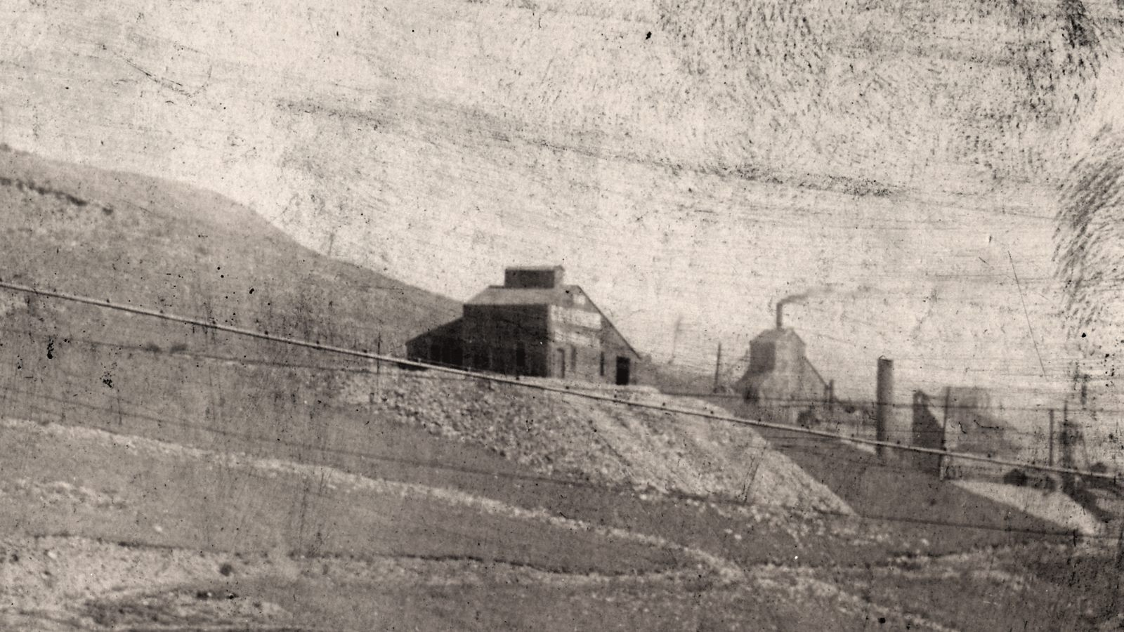 This badly looking image is the best I have of this mine, the Shaft House of the Chesapeake Mine as it was seen in the background of a photograph of a troop of Soldiers, possible the Denver City Troop, as they posed at Camp Goldfield sometimes around 1903. The Mine is in the center of the view and was located on Battle Mountain below the point where the Golden Circle crosses over the Midland Terminal tracks to work itself up passed the Portland Mine, and just outside the bottom part the tents of Camp Goldfield start showing up.
