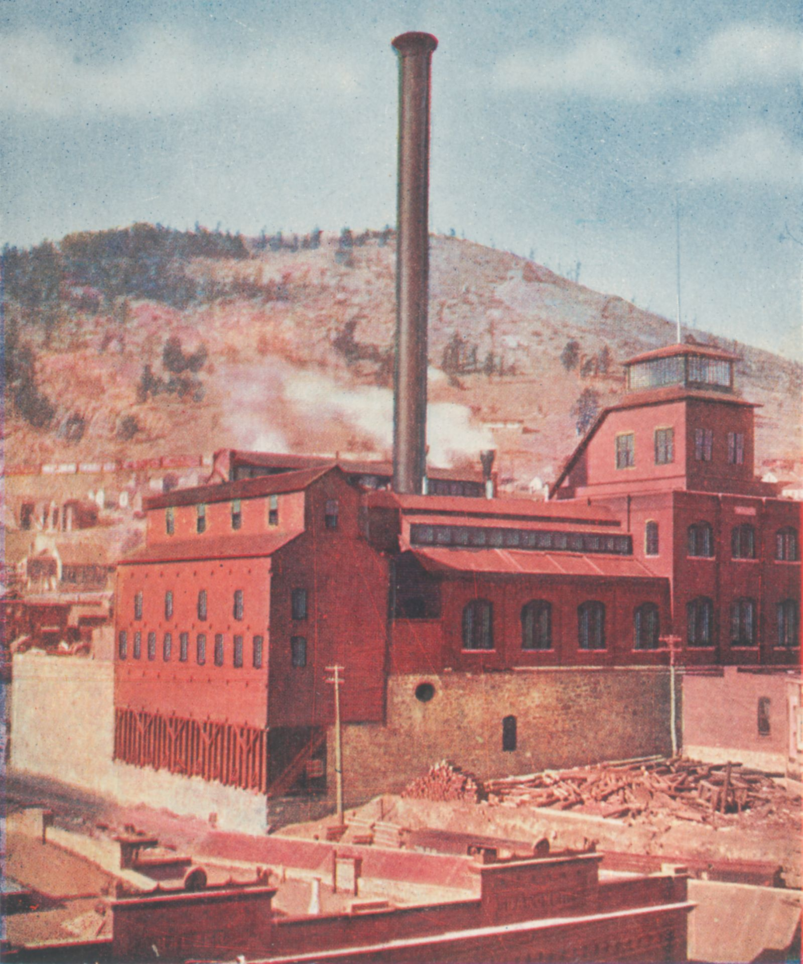 This view shows the Gold Coin Mine in Victor in all its glory, focusing more on the Ore-house. One get to see the foundation walls which still for the most part is still there in Victor, with its brick based shaft-house with the stained-glass windows and tower like part over the top of the head frame. The smokestack is very visible in this view, and in the background, is the Squaw Mountain seen, with the mainline of the M.T. seen just behind the top of the orehouse.