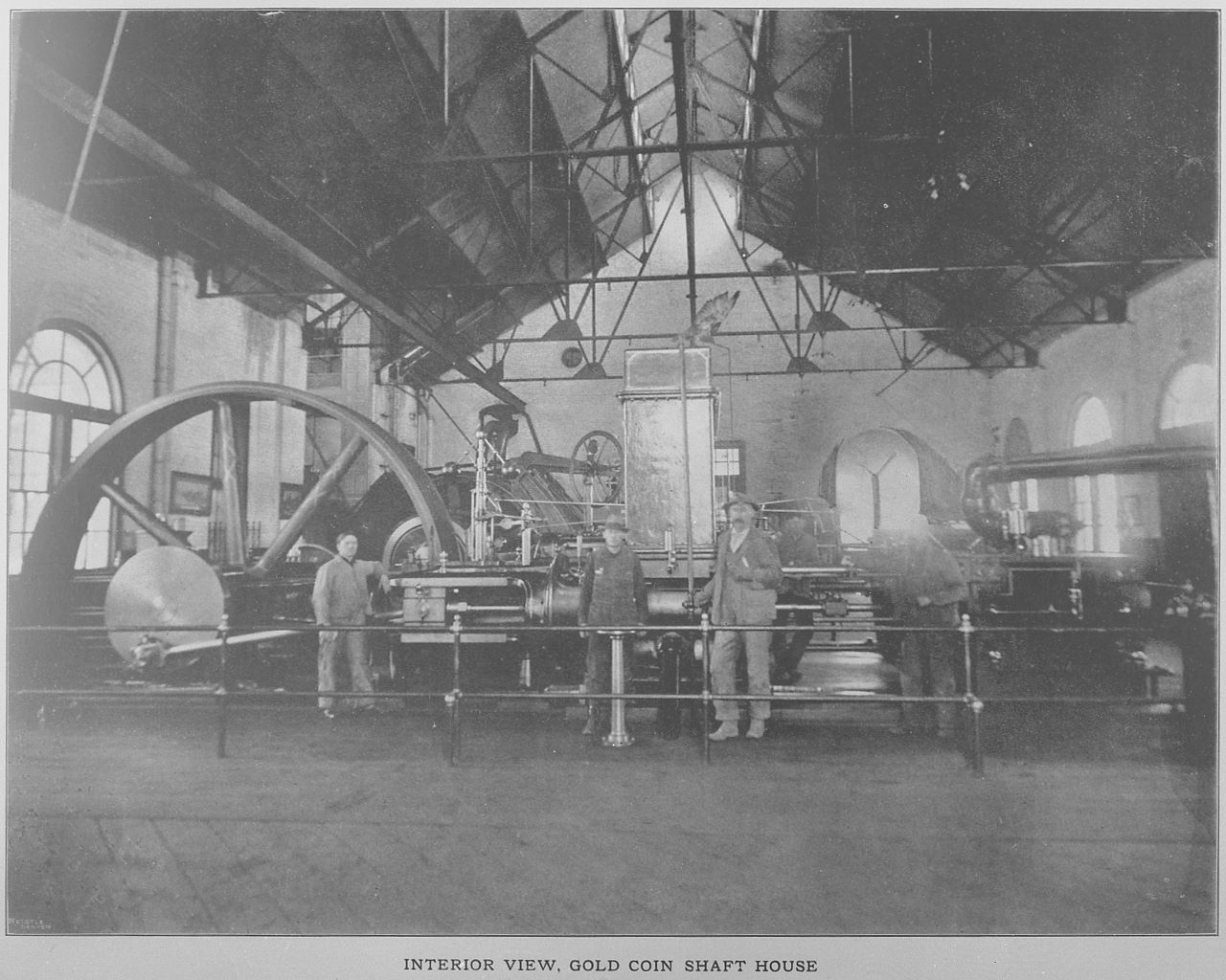 This view from inside the engine house, the west and north long structure from the shaft house, shows part of the massive machinery in use in this mine. We are looking towards south, with the piece just behind the men possible be the Fairbanks-Morse pump the Sanborn 1908 Fire Insurance map is mentioned in this area. Or it might be part of the compressor plant as mention both in Sanborn and in another view, I have from opposite direction talking about the compressor plant in the location of the photographer. Either way, further into the photo, behind the machinery with the flywheel, is the massive hoist of the Gold Coin, with the opening towards the shaft seen as a large opening through the right-hand side of the large flywheel of what I think is a pump.