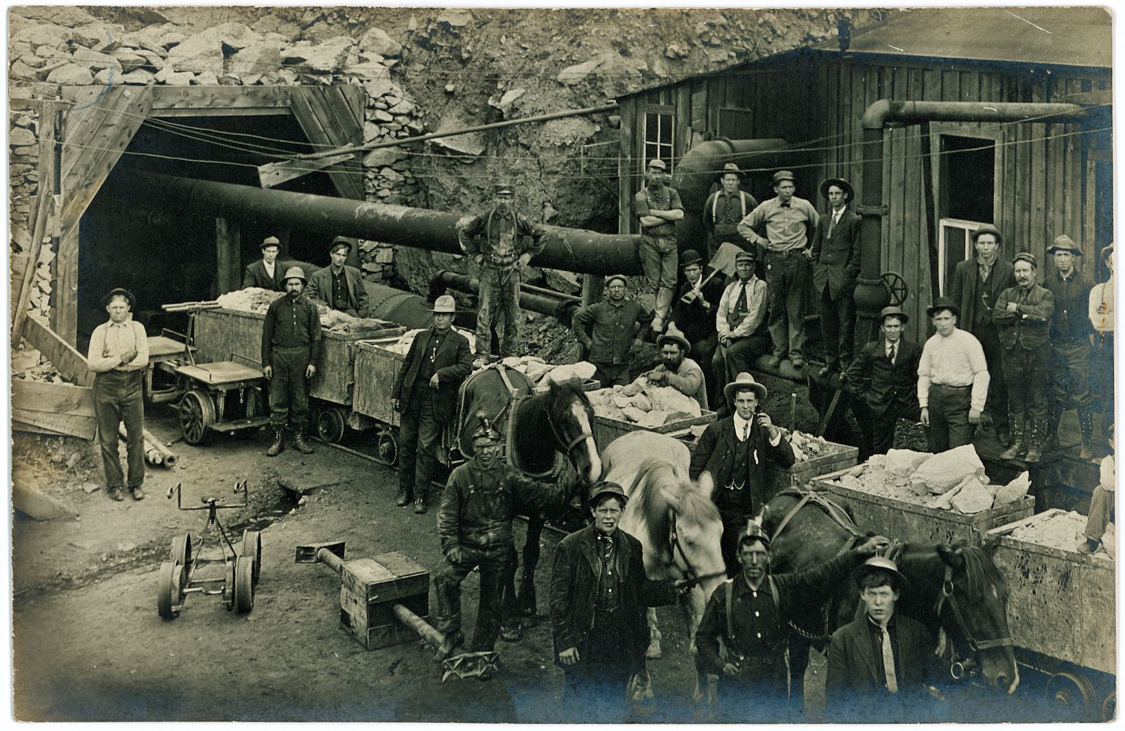 This Group-Photo of workers, management and equipment at the Portal of the Roosevelt Drainage Tunnel during its construction has been used in an article in the July 1914 edition of the Mining Science journal/magazine, so it predates that date with an unknown time. No names given in neither of my sources for this image, but there are many men here.    Image shows 8-ore-cars filled with rock from the tunnel work, also three horses are held in front of the cars, uncertain if they where the motive power used to haul the cars out of the tunnel. There are also some other foot powered rail cycle types shown, a shed makes up some of the background, a compressor building of some sort as there is a large pipe coming from it into the tunnel opening.