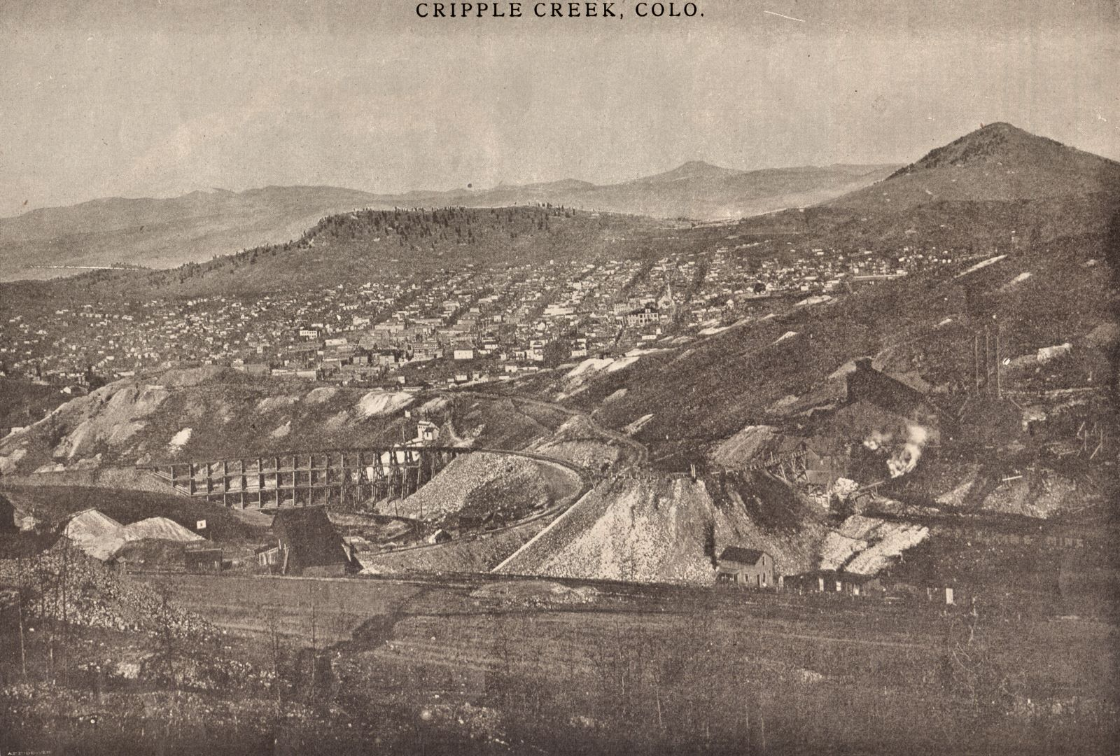 This view across Poverty Gulch, towards the town of Cripple Creek, is photographed on Gold Hill a little uphill from the C.O.D. mine. The Short Line main line is climbing the hill via the curved trestle seen on left-hand side, and the original High Line electric trolley line is partly seen on the left side of the railroad curve, after gone through the trestle on its big climb up Gold Hill. * The Reno Mine is seen beyond the Short Line trestle, almost center bottom/top and about 2/5 in from left-hand side. Near the upper end/right-hand side of the Short Line trestle. * The old shaft house of the C.O.D. mine is seen from behind, about 1/3 up from bottom and a bit more than 1/3 in from left-hand side. * The Gold King, or the El Paso Gold King Mine, is seen center bottom/top about 1/5 in from right-hand side, in the darker shades of this image sadly.