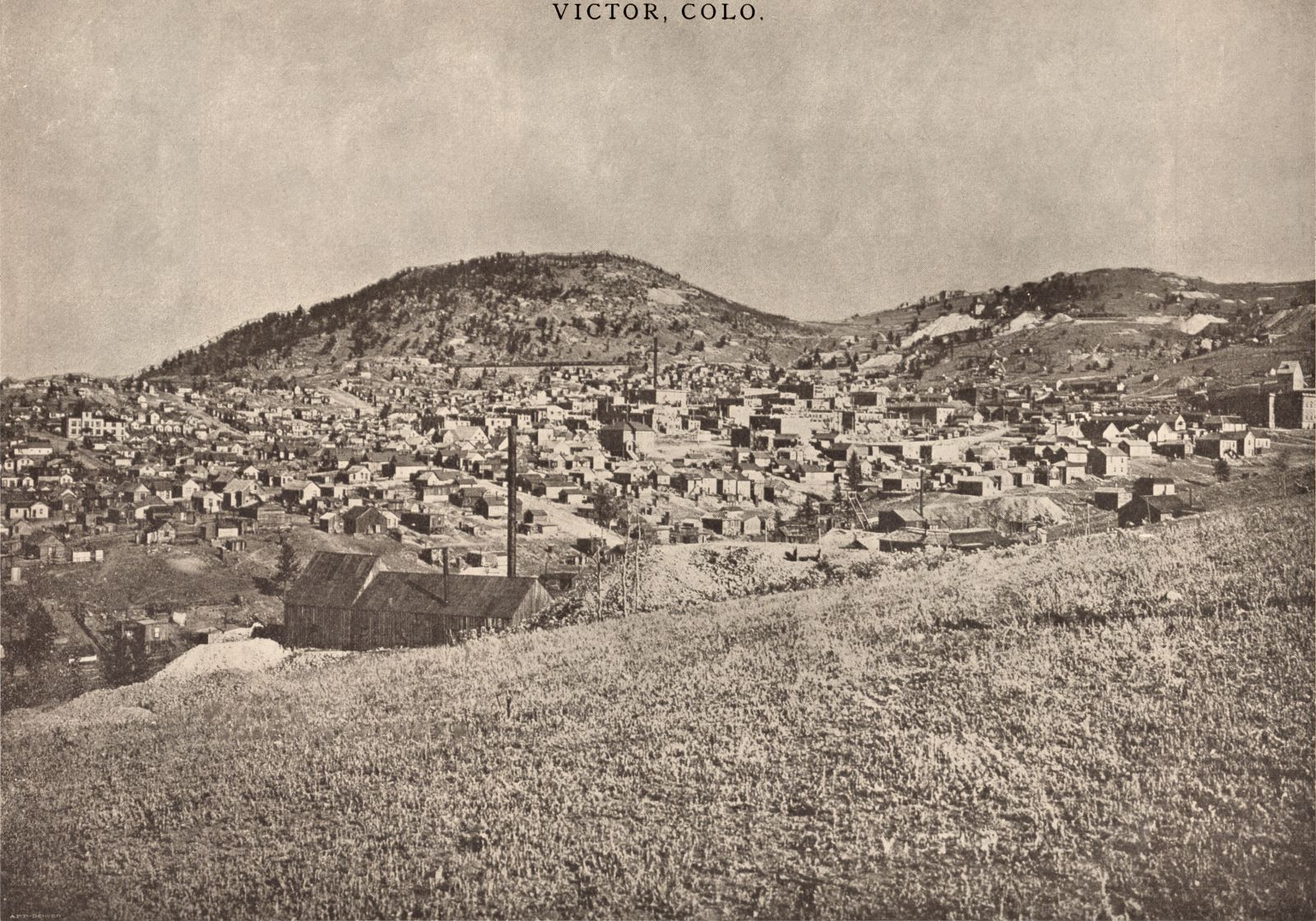 "This overview of Victor as seen from somewhere in South-East  has been credited to several photographs, Schedin & Lehman is written on an Image seen at DPL, where also Julia Skolas has her name, but as this view is from after the 1899 fire which took out much of Victor, but before the head-frame of the Gold Coin was covered sometime in 1900/1901 timeframe, I can't see how she can have actually have taken this photo, so I think she bought it and the rights to it – and possible others – from the Schedin & Lehman company after she arrived at the District. The usefulness of this image is really on the DPL view, as most of the mines are deep into the image and some of them are really not much to actually see anything other than knowing they are in this view in order to help place them in a mental map of the District/area. * In the foreground left is the mine I've seen a close-up off from the other side, where it then was marked as ""Great Central Mining & Milling Co."", and from other sources I have it linked as being named/known as the Maggie Mine. * About middle bottom/top along the right-hand side is the top part of the Shaft-house of the Strong Mine, with the Victor High-School in front of it. * About 2/5 down from top and about center left/right is the large smokestack of the Gold Coin mine, with the Head-frame at right of the smokestack – best seen on the DPL large image. This helps date the image except I don't know the date the head-frame was enclosed in the brick structure most common known as the Gold Coin mine. * Above the smokestack of the Gold Coin, high up on Squaw Mtn. is a dump area seen, there is a small Shaft-house there, again I refer to the DPL as best view, that is the Nellie V. mine. * About 1/4 in from right-hand side, and about 1/3 down from top, is the large Ajax Mine complex seen, with the big dump out over the hillside of Battle Mountain. Looking at the DPL view one can actually see they are extending the Ore-house towards right in this view. * Just right of the Ajax is the upper shaft of the Dead Pine, located along the Golden Circle, they did as the Portland Mine did, they have a tunnel over the tracks of the Golden Circle narrow gauge line, except here it is made of wood, not steel as on the Portland property. Can't say it is on the view, I know it is there, seen as a dark spot between Ajax and Dead Pine, but it is too far away to be of any use at all. * Further to the right, just left of the massive Portland dumps, where the hill curves, there lays the Granite Mine, seen with its Shaft-house and power house, smokestack and all, albeit at a to large distance to be of any good use for a model work, it helps in determining where in the area it was located. * The Dillon Mine has actually two shafts seen in this view, again it is the DPL view that is really of any use to such image research, a slight distance left of the shaft-house of the Strong mine on the right-hand side, there is a small Head-frame and small hoist house seen on the hillside with a dump – that is located on the Dillon claim. Further up the hill, more hidden away due to distance and such, is the more commonly associated boxy type of Shaft-house of the Dillon seen where it lays just below the mainline of the M.T. climbing the hills towards the Portland mine area outside the view at right. Seen best on the DPL view at a 100% look, or try the 200% and go near right-hand corner, the only shaft-house in this area with lettering on the side of the structure. * Again, the DPL is of help to locate the Ore-house of the Mary Cashen Mine, as it is poking up among the roofs of Victor structures, about halfway between the Strong and the Gold Coin mines. * Also, on the DPL Image the Fortuna Mine is seen quite well in the 100% view, just where the word 'Skolas' is written about 2/5 up from bottom and about 1/3 in from right-hand side. Showing a small Head-Frame west of the Hoist & Power House, with what might have been the loo west of the head-frame or possible a shed for dynamite?"