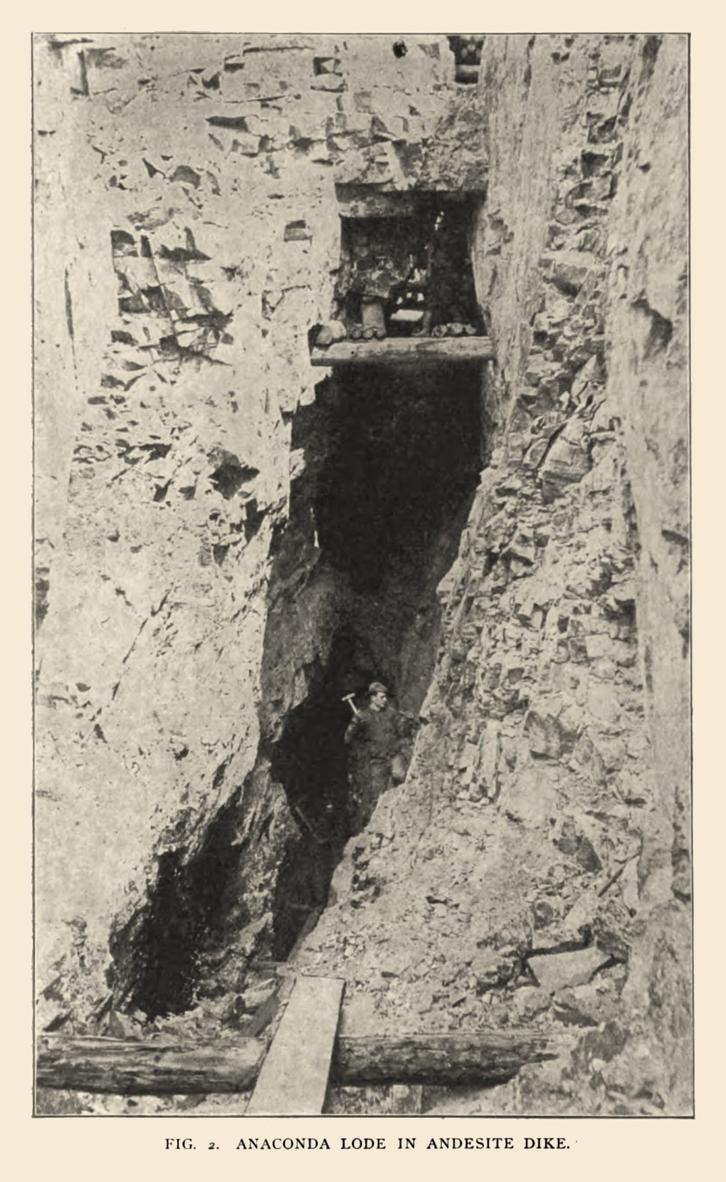 This is from a photograph of the Anaconda lode as seen in an open-cut in July, 1897. The lode at this place forms a part of an andesite dike traversing the breccia. The dike exhibits a multiplication of fractures parallel to its walls, and along these lines of cleavage there occur seams of quartz and fluorite carrying tellurides.   In the surface workings, the gold liberated from the tellurides occurred pseudomorphic after sylvanite, distributed in yellow patches amid purple fluorite, affording specimens of great beauty.