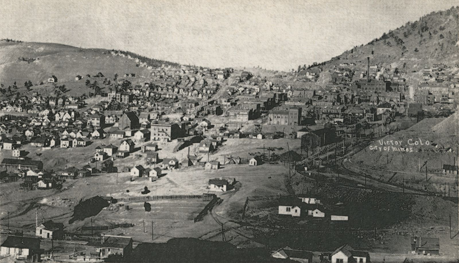 This view of Victor town is taking from east, looking west, sometimes after December 1905 as that month saw the sale of the Gold Coin Mine to the Granite Gold Mining Company, which in this photo is now marked as Granite Mine. The mine is seen about 1/5 in from right hand side, and about 1/3 down from the top. Further down from the Gold Coin is seen the tracks of the Short Line/High Line and the Florence & Cripple Creek, and the Golden Circle track is also seen. The Short Line is the left most, on a big fill after crossing the F. & C.C. track outside the view at right lower about 1/4 up from bottom. The yard of the Short Line is seen better in my postcard copy then in this bad print view. The Golden Circle track leaves the F. & C.C. at left of the text reading the title of this view, and is the part first seen under the title text at right hand side of this view. The group of buildings/houses inside the fence in the foreground right is the Stratton's Home when he was staying in the District after making his millions as per Mr. Spell in his book. Somewhere at left of center of the photo is the dump of the Spicer/Rexall mine seen, in my postcard view I can see it a little bit better but not that easy, appears to be a crib wall around it. It would be located just below a line between the Garfield School (the large structure with the tower about 1/4 in from left-hand side and 1/3 from top) and the Gold Coin mine so to speak, about 1/4 on that line towards the Gold Coin.