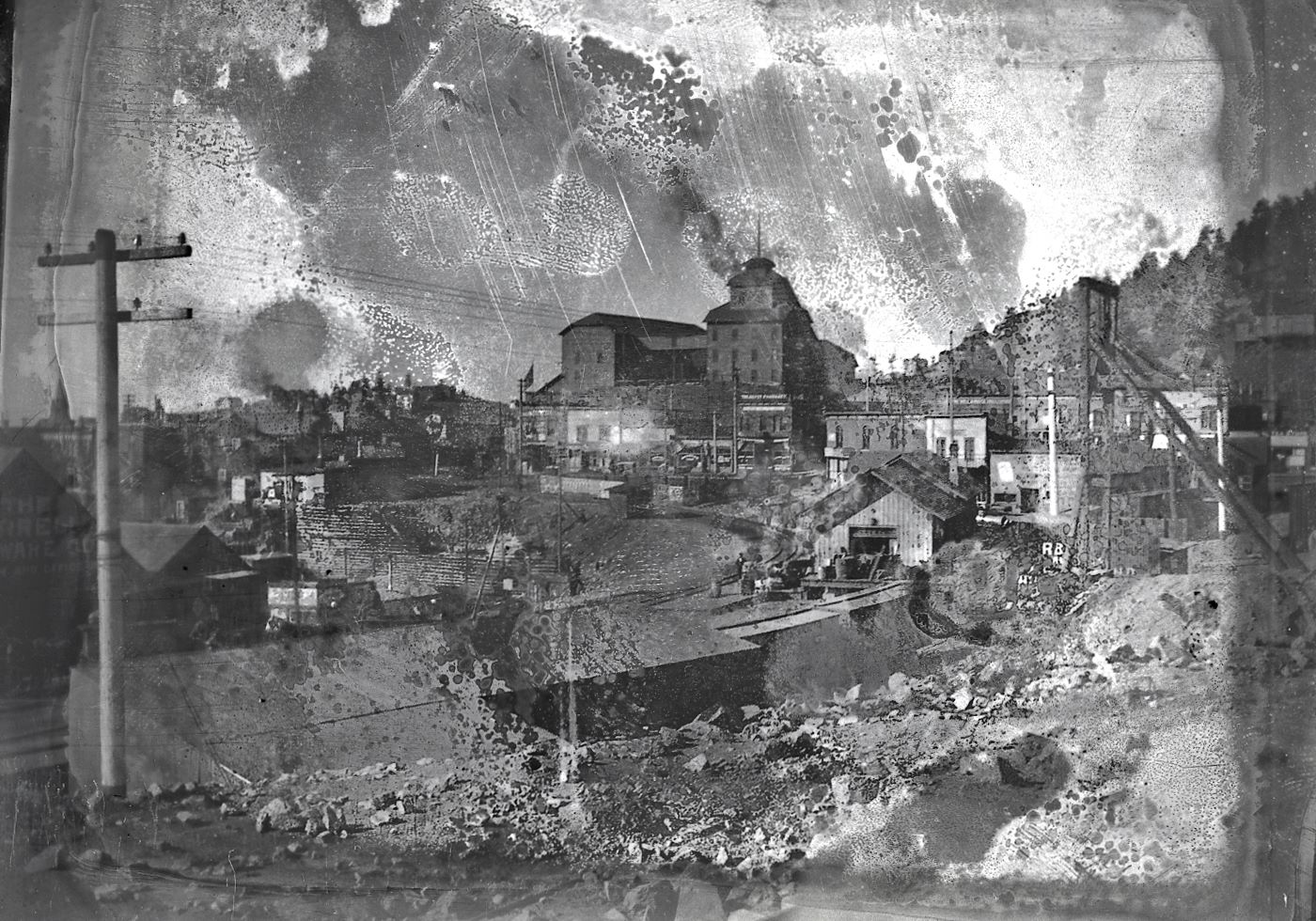 Sadly, this is a really bad quality glass plate negative, lots of damages to it, no idea if it would be possible to clean up or not, looks like there are some sort of fixed dust to it, maybe the right type of cleaning would do wonders? But I have not the correct training or idea how to proceed so I just scanned it and put it aside, feeling sorry it was so bad after being stored away a hundred and so years. Sad really, as this would otherwise have been an excellent view towards the Gold Coin Mine from the east, before the fire that burned it and much of Victor down.    The head frame in foreground right, I am not sure about, it might be an early prospect shaft of the Mary Cashen, or possible some other mine in this area, so for the time being [19.02.2017] I just assume it to be part of the Mary Cashen.    The railroad seen is the Florence & Cripple Creek with its depot like it was before that to burned in 1899.
