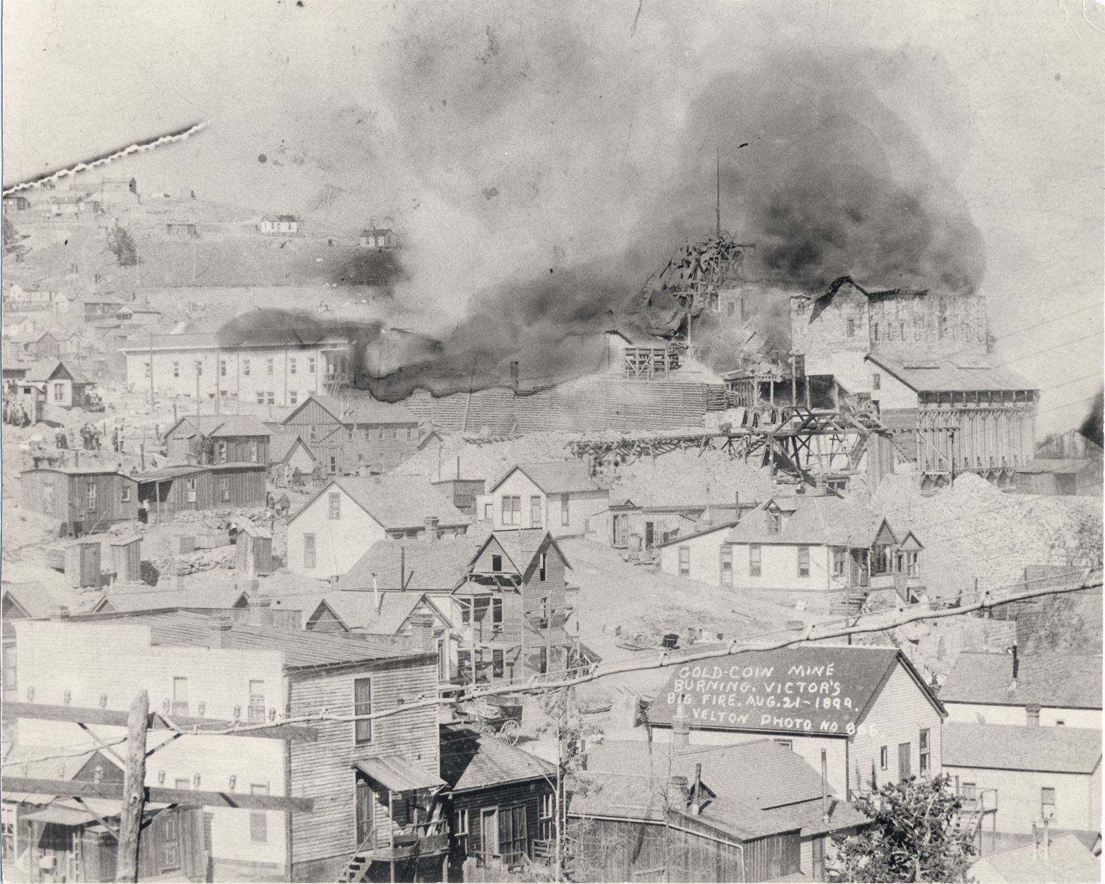 "While this photo has some damages done to it, I still think this view tells the story of the old Gold Coin mine, the one burning this fateful day, quite well! There is a story in a book titled ""Cripple Creek District: Last of Colorado's Gold Booms"" by Jan MacKell (Collins) where there is included a letter by J.A. Small to his wife, mention how he and unknown others escaped the flames through the ore house via the trestle, over the tracks – same trestle as seen in this view. What a feel they must have had, mine burning down behind them and nothing they can do!    This view also captures part of the town of Victor, how much of this is taken by flames I can't tell you, but I see at least one house is under construction, around center of the photo, a little left and down from center, three levels including the part under the roof of what is nearly a tower itself.    Many people are looking at the Gold Coin, and in the house seen below the trestle coming out of the ore-house of the Gold Coin, a lady stands on the porch, wondering over something I presume."