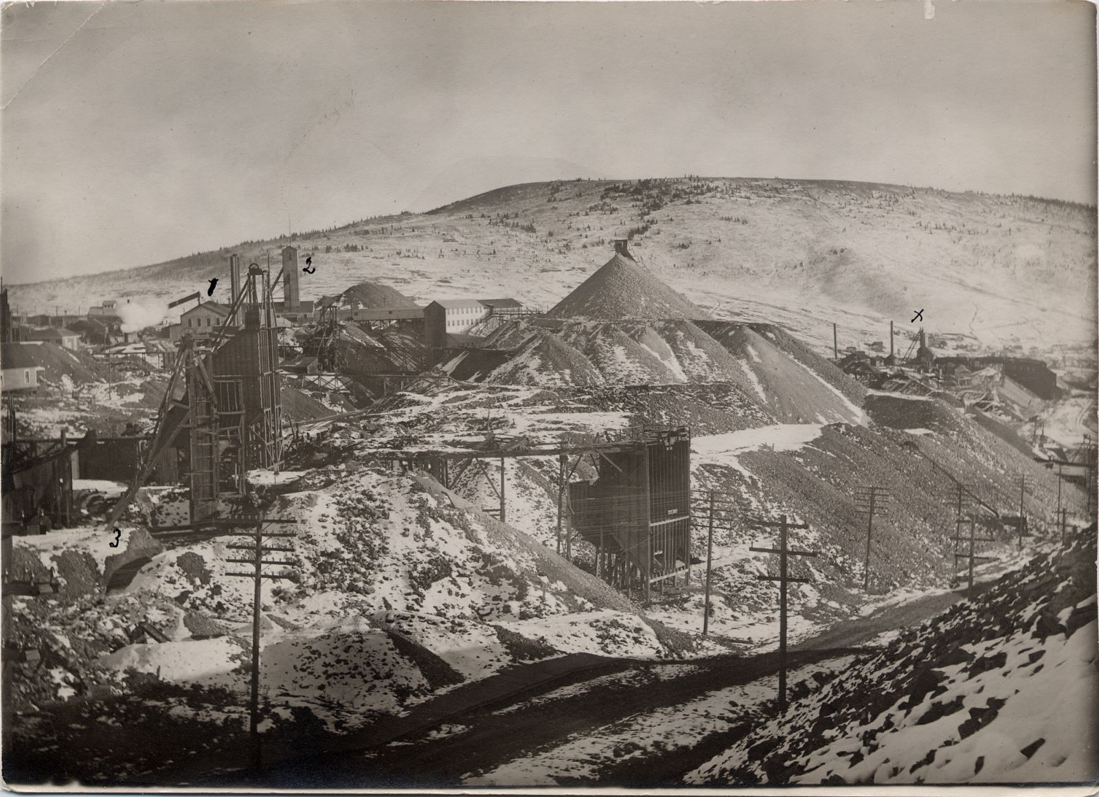 --- Text on backside:    No. 1 - 2 - 3 are shafts of the Vindicator mine, which is the largest mine here. They work a great many men. Have one mill here and one at the Springs. They are building a new one here that will use the new oil flotatation system.    X Was the Golden Cycle mine, it now belongs to the Vindicator.    These mines have produced many millions of dollars, nearly as much as the Portland, and have still millions in sight. --- End Text on Backside --- -> I've seen it mention in a mining magazine from May 1915 that the Golden Cycle was sold to the Vindicator, hence this image must be from sometime after this timeframe.