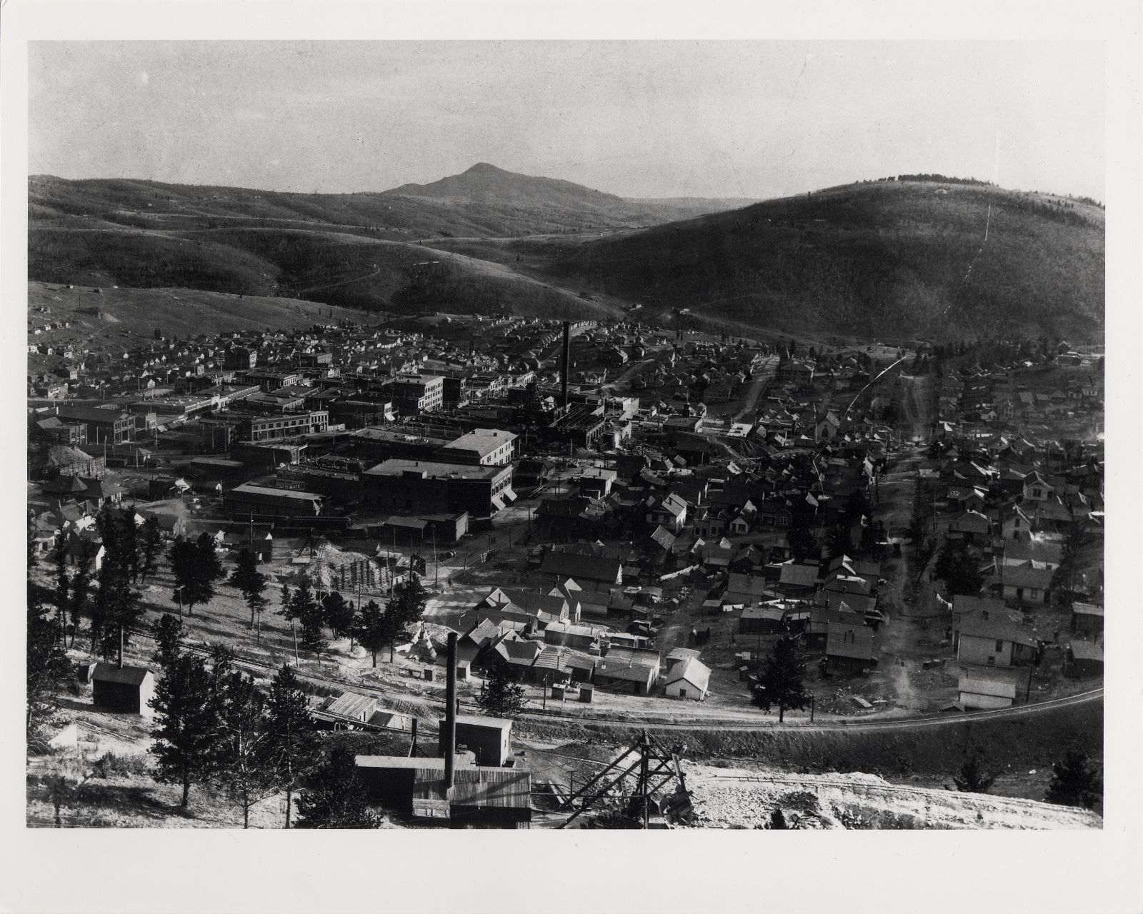 This is a photoprint version of a glass negative that I also have, it is a shot of Victor from the area on Battle Mountain closing in on Squaw Mountain.  There is an unknown mine to me at the time of this writing [18.02.2017] in the foreground center bottom, then the Midland Terminal main track comes on a filling crossing over from the Battle Mtn. to the Squaw Mtn. hill side. Further downhill, about 1/3 in from left-hand side, and about same from bottom, one see a crib-wall in a curve and this is where the original High Line entered Victor town, track is seen there as well. To go to this location, the trolley had to use a tunnel to cross the ground of the Dead Pine mine with its dump and a big crib wall - I have seen on a Sanborn map an indication of a tunnel there too, and for me, this picture helps now to show how it looked in that area. One another thing I like with this photo is the fact that I can see Gold Coin under construction, I can see the Head Frame, the top of the brick structures is open, and only thing that is covered is the ore house. Way down, in topology below the Gold Coin but in this image, about an inch above the Gold Coin, to the right of the smokestack, is the Shaft-house of the St. Patrick Mine visible as well.