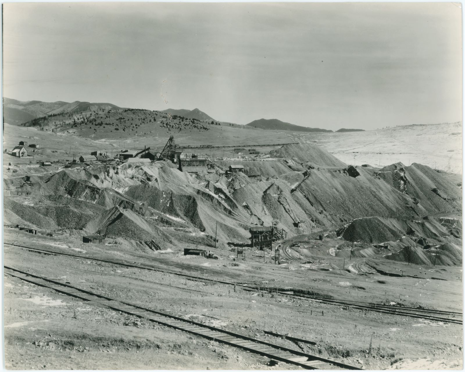 The Date of 1934 comes from the backside of this image, where it been handwritten together with pieces of text as this came from a Newspaper Archive, mention Sunday Section and what I think say 3 columns, no Newspaper name mention.    This view towards the Vindicator Mine operations, on eastern part of Bull Hill, has some of the still existing Midland Terminal tracks in the foreground, which at one time in the past might been part of either the High Line Trolley operations of the Electric Division of the Short Line, or even possible the narrow gauge Golden Circle operation, as this view is from near the Last Dollar mine, just can't tell exactly where.    The Vindicator Mine dominates with its huge dumps the more background part of this image, with a huge string of boxcars in the Bull Hill Yards of the M.T. making up the background scene behind the more top part of the headframe of the Vindicator, and of course the mountains in the horizon background.    About 1/3 up from bottom and about 3/7 in from right-hand side, there is a large Ore-bin or an Ore-house, that might have been part of the Longfellow Operations, where there is also a smaller headframe this side of that bin/house visible not too far away. Across the tracks seen curving away toward right is where the former Independence Depot along M.T. was located.