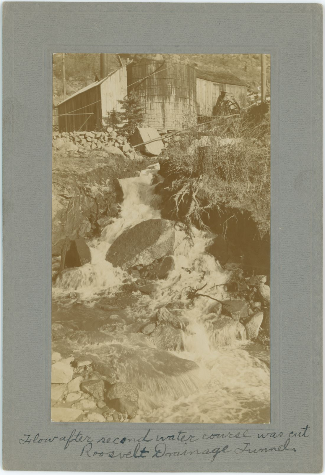 Photo is marked as showing the Flow of Water from the Roosevelt Drainage Tunnel after cutting the second water course, but as there is no date given it is hard to judge any date this might been taken, but I assume this view is from when they hit the second water course, possible around end of 1908.    In the upper part of this view is seen support structures at the portal area, when comparing this to the image showing the First Flow there is now a shed around the smokestack seen near left side of the before mention image and also seen poking up from the roof just left of the water tank near upper left. The water is coming from the tunnel, located behind the shed, which in turn is behind the water tank seen.