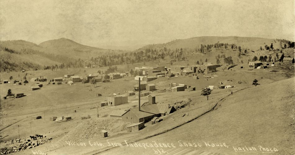 This view of an early Victor town, taken from the Independence Shaft House, shows quite a large shaft house of the Strong Mine up front where it lays on Battle Mountain. There has been done some grading for the soon to come F. & C.C. railroad below the mine, and further west, as there is a fill seen just west of, or at the spot, where the Victor Depot was to come. Further west, near the right-hand side, there is a cut seen and the street in front of that cut is to be known as 4th Street and the future site of the Gold Coin operations. Sanborn for 1894 (December) shows the St. James Hotel here, and I think that is what I read on the full view seen at the DPL link for the structure seen at right of the cut. All this make this an early 1894 photograph due to the grading done for the railroad. Possible around March, or April, but before end of May as by the 25th of May the Strong Mine is blown to pieces to set an example during Labor conflicts in the District.