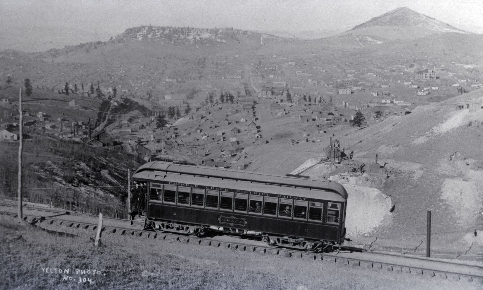 View is a negative type of Photo taken by a camera of an older type of Photograph, with not the best quality film so it is rather grainy sadly. But, the view is nice, of the Trolley car named Grace climbing Gold Hill high above Poverty Gulch, along the original steep High Line grade. * The Smokestack poking up near lower right-hand corner behind the Trolley is part of the Chicago Tunnel operation, while the two Head-frame type of mine operations seen just above the lower end/back end of the Trolley is as far as I can tell operations on the May Queen lode claim on the left and the Granite Hill lode claim on the right. * About middle top/down and about 1/4 in from left-hand side is the structures of the Abe Lincoln Mine, and way down in the gulch one see the M.T. Wye Trestles and to the left of them is the spur to the top of the Midland Sampler seen cutting up the hill from a spur a little down from the Abe Lincoln.