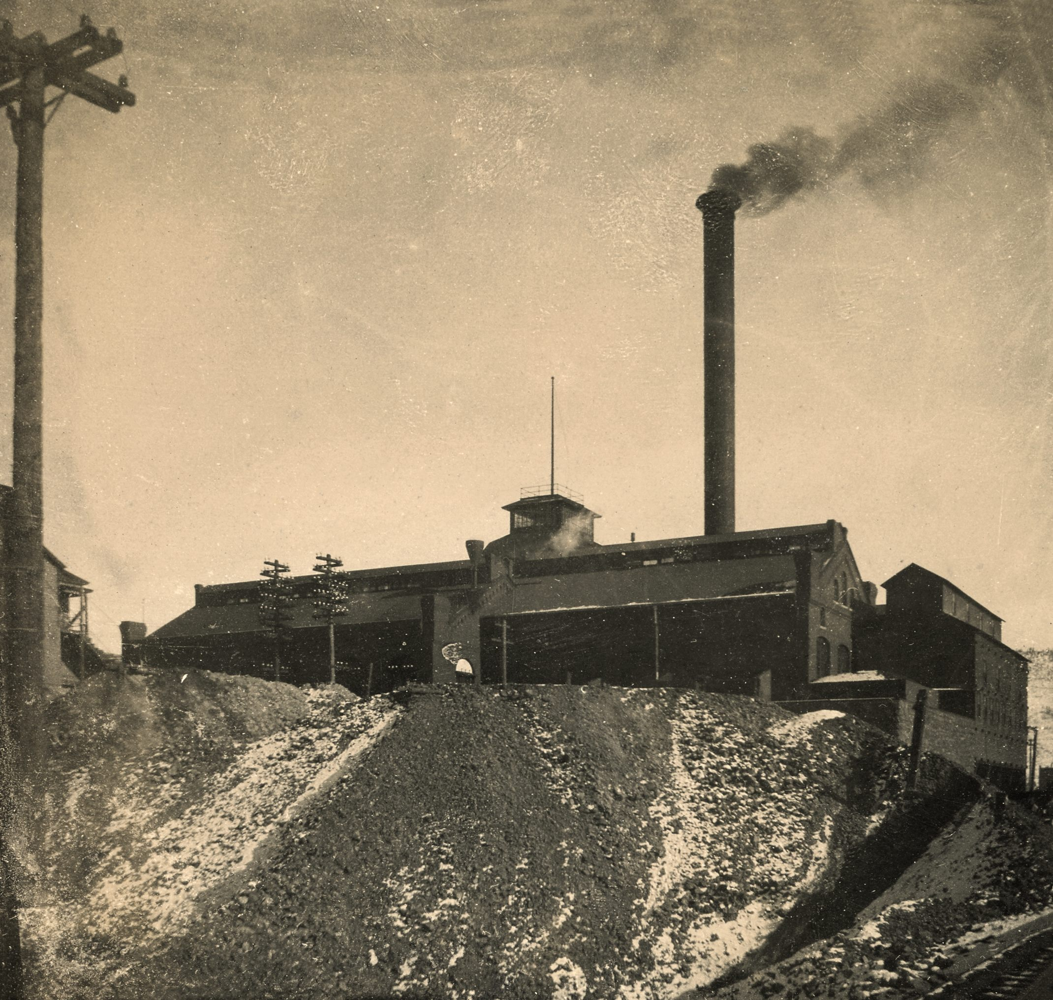 This view of the Gold Coin Mine is taken from the roadbed of the F. & C.C. railroad, as seen in lower right corner where a piece of the track is visible. While the sheet this image was pasted into has an 1898 date to it, that is plainly wrong as this is the brick version of the mine, and that only happen after it burned in 1899, so I think this is more like 1900, but I can't date it more precisely, sadly.    The version shown here is enhanced to fix some fading issues on the original, in addition to me using a perspective filter to make the sides of the structures more appealing and level, making me having to crop the image a little of non-important pieces, and I also had to paint in some extra sky and track pieces, but I think it gives the credit to he source image as it should do, a view of the mine as it would have been seen from the Florence & Cripple Creek tracks west of the mine!