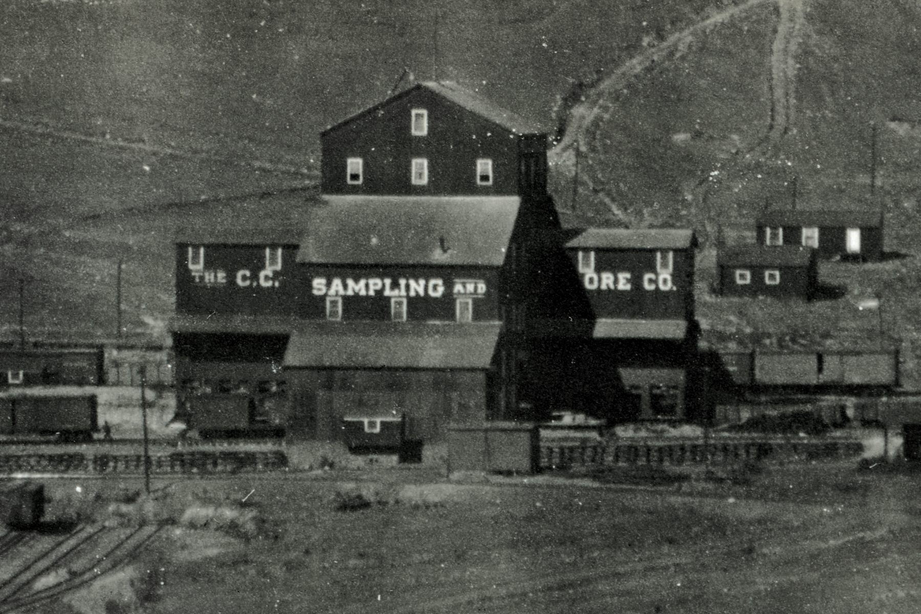 Sadly, not the sharpest view, but I felt this 1200dpi crop and enhanced version is still one of the best views I have of the 'Black Sampler', of the Cripple Creek Sampling Company. The Sampler was also known as the Cripple Creek Sampler, or Bull Hill Works, Bull Hill Sampler, and other names it appears.    Located just beside the Midland Terminal Mainline, it was at one time served by dual gauge as the Golden Circle railroad also had a spur here. Also served by the Short Line I assume as it's Mainline runs straight passed it on the west side (behind it in this view). The photo is from the timeframe the Sampler had Dual Gauge I assume as there are Dual Gauge down to the T. & B. Sampler which is outside this cropped view at lower left.    There are 4 or 5 levels of tracks seen in this view, from the small stub-yard at the T. & B. Sampler seen in lower left, to the M.T. Mainline seen about 1/5 up from the bottom, where the southern leg of their Bull Hill/Victor Pass Wye is seen going down towards lower right-hand corner. Then the 'out business' level of the Sampler is seen, built up on a small crib-wall as I assume there was no room left for a fill due to the closeness to the M.T. mainline. Next level would be the 'business in' level, where there are seen a combination of Boxcars and at least one Gondola car in the view, about 1/3 up from bottom. Last level, if it is a separate level, would be the Short Line mainline grade, I think it is at a higher level but hard to tell for sure on this view.