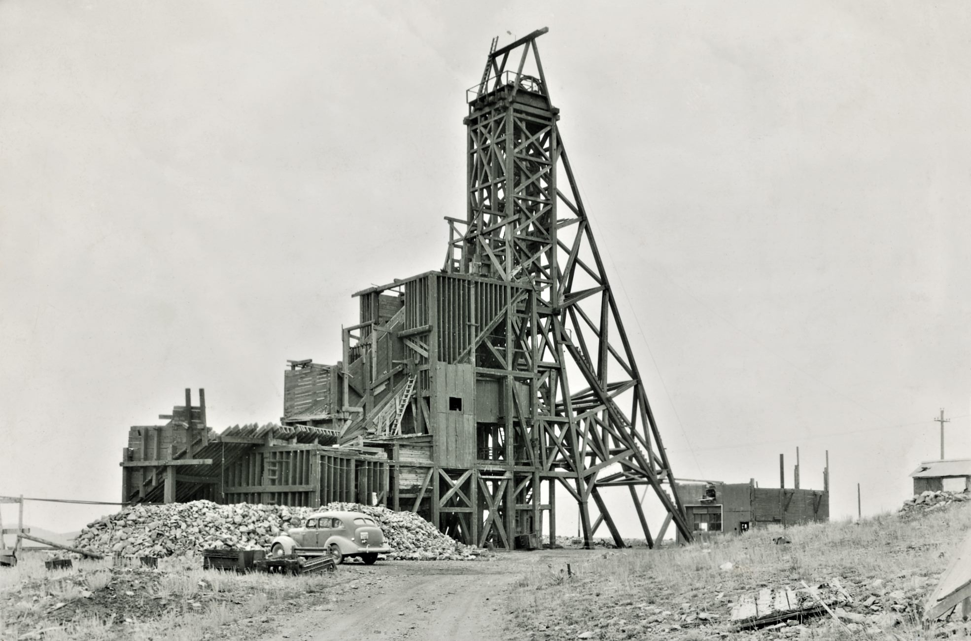 This somewhat enhanced view at the exposed Huge Head-Frame/Gallows-Frame of the old Stratton Independence Mine on Battle Mountain, outskirts of Victor, Colorado, show quite well how Huge the whole structure was! Dating this view is hard, I think it is from around 1940, but I do not know. There is a car parked below this mine structure, and that seems to have a License-plate of 43-660 but I can't tell what else it might have written above the numbers, so I can't date the image from that either…    The whole structure is quite massive, and all in wood it appears! Hard to imagine all this at one time enclosed in a massive Shaft-house type of structure, as I assume this is as it was built inside the structure back in the days. The left most parts, with the various bins I do think is more recent then the headframe itself, but I dare not say anything as this is beyond my knowledge.