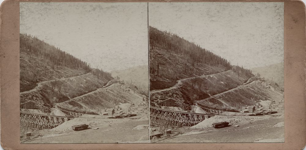 This view was taken just above the M.T. trestle crossing Eclipse Gulch, and it shows on the left side of both images an early look at quite a large shaft house of the Eclipse Mine, and how it is located between the roadbeds of the M.T on the upper side and the F. & C.C. on the lower side. It also shows a moving train on the F. & C.C. with some of the settlement known as Eclipse below the railroad grade, including an unknown mine and of course the Economic Mill way down the Eclipse gulch at the right-hand side of both images making up this stereoview.    Photographed around 1899/1900, as the mill was built in 1899, and as I see no traces of the Low Line, which was built in 1900, this was photographed in that timeframe.