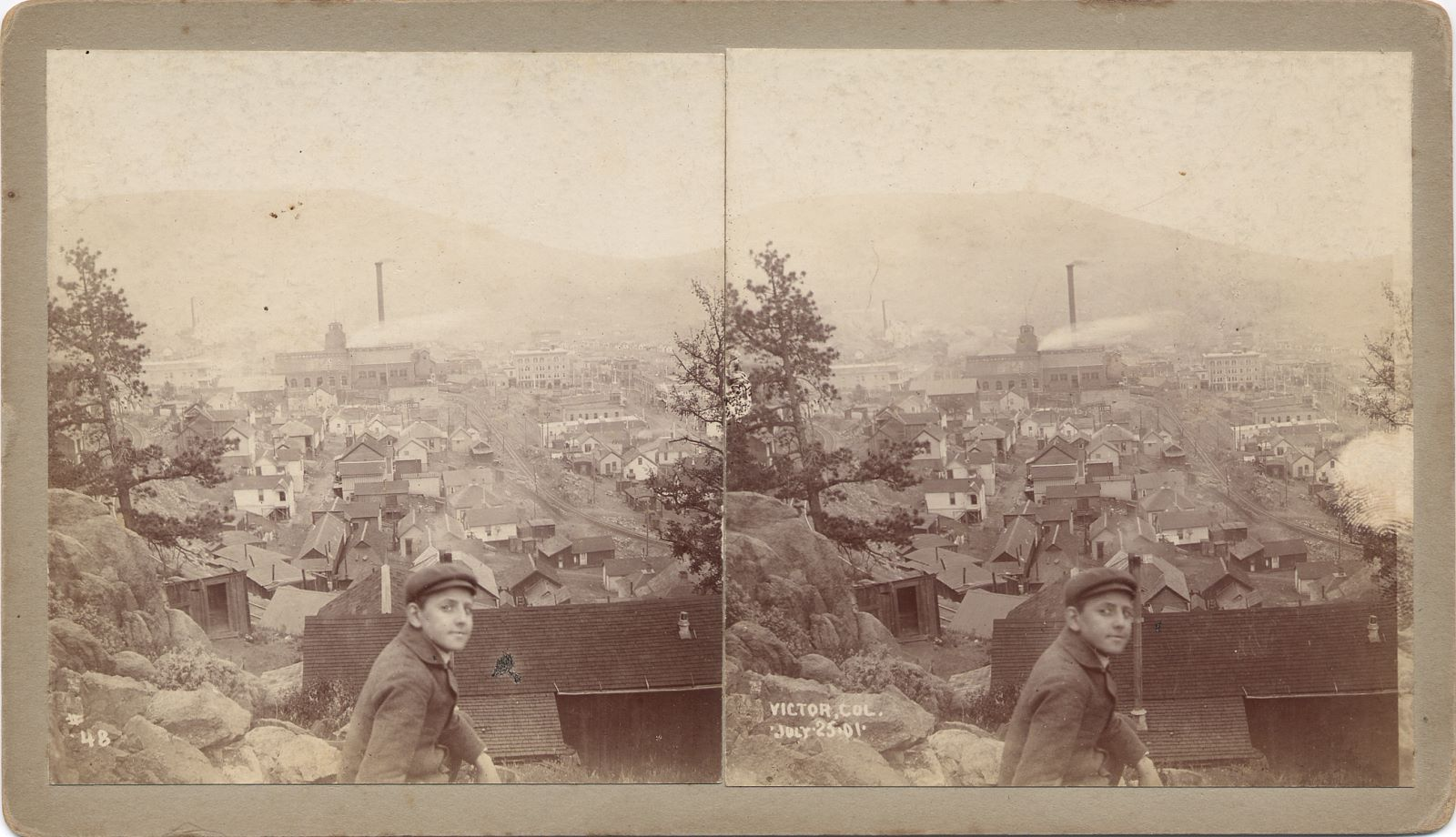 This view of Victor, from just above the M.T. spur down to Victor depot, on Squaw Mountain, is a nice one as it is dated and hence help show how for instance the Gold Coin looked in July 1901, as when the photographer R.I. Dabb of Le Mars, Iowa, took it on the 25th. * Sadly, it is quite faded in the background, but to the left of the Gold Coin is the quite large and bulky shaft house of the Strong mine seen in the distance, and that is of help to date views of the Strong mine as well, making this an important view, even if the Strong mine itself is not that easy to see details on. * The Gold Coin looks fully put up in bricks, all roofs and walls are there, the ore-house looks very narrow in its width when compared to the engine-house, boiler-house of the Gold Coin, but almost same width as the shaft-house. The roadbed of the F. & C.C. is coming through further downhill, and passing by the Gold Coin with two sidings branching of outside the ore-house, before curving out of view behind the mine.
