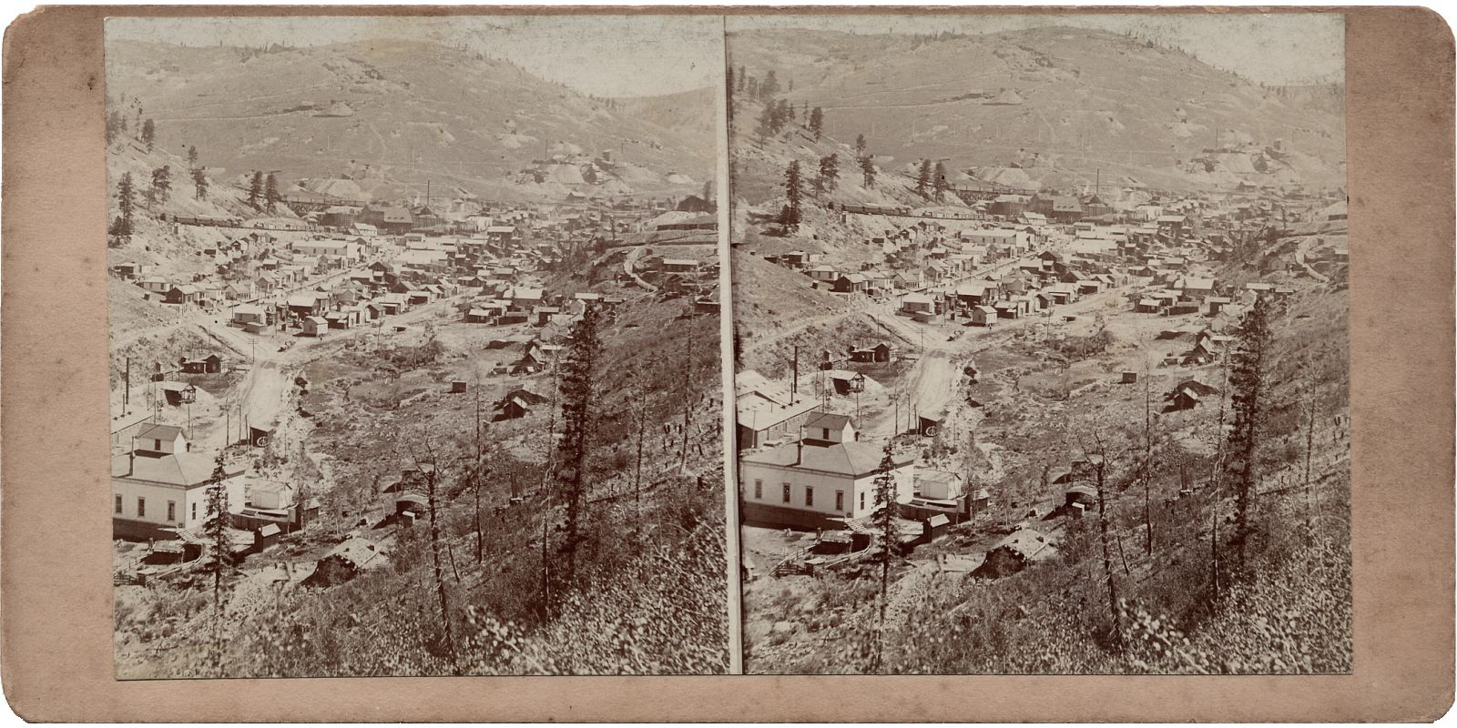 This view from an unmarked Stereoview is showing the town of Anaconda with the School House and part of the Hartzell Mill in the foreground left. In the background is Gold hill and some of its mines, while the town itself is located near the Anaconda mine. Anaconda mine is about 1/3 down from the top and about middle-of-view in the left/right direction. About halfway up on the left side is the Ore-house of the Blue Bell mine just above the school house cupola.