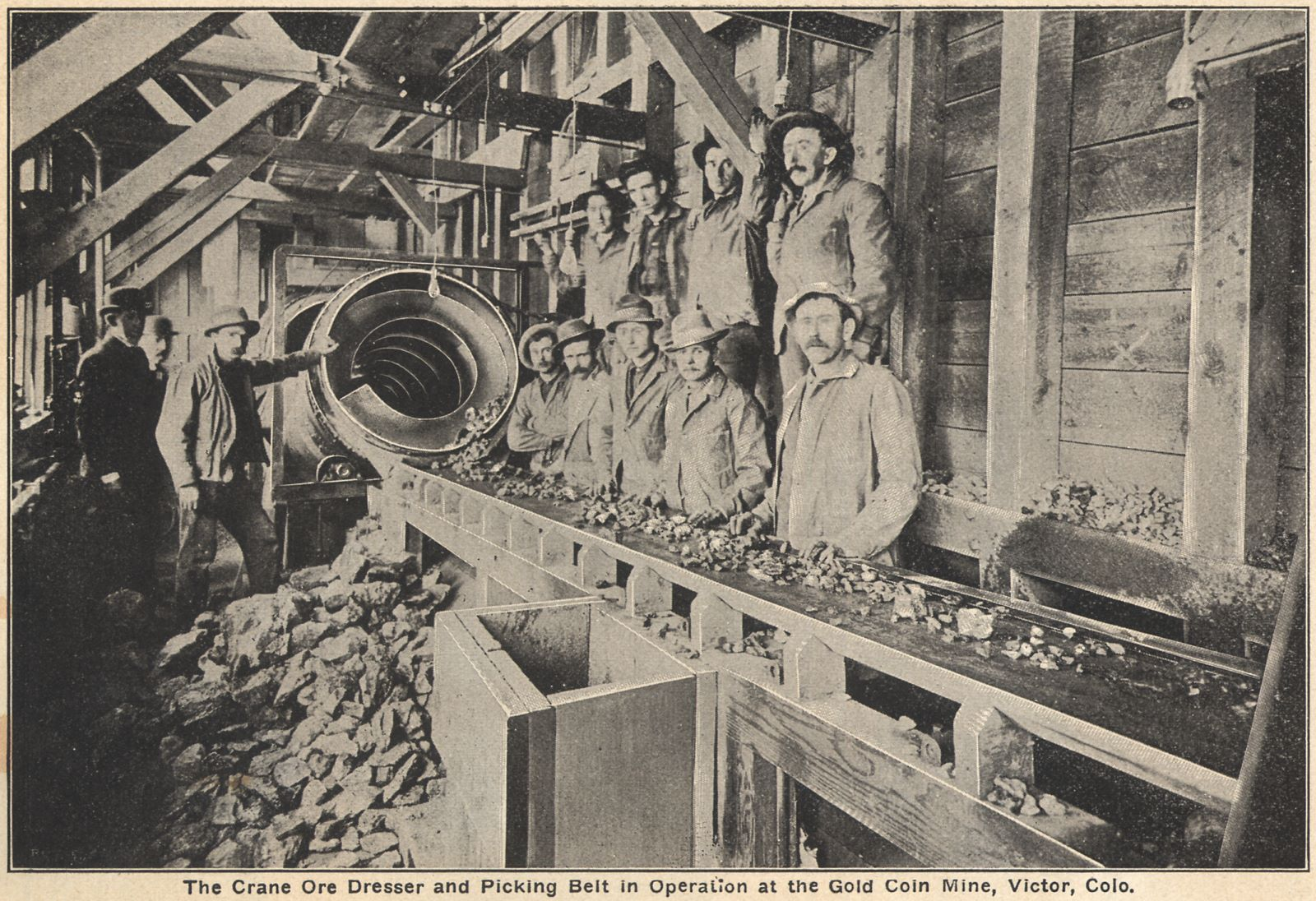 "This image is used as an advertisement for the Crane Ore Dresser in all ""Seeing Cripple Creek"" issues I've seen, and is said to be in the ore-house of the Gold Coin mine in Victor, Colorado. No idea how old the image is, I just notice all the wood in use and keep wondering how that ties into the brick based ore-house of the Gold Coin mine I most often see in images."