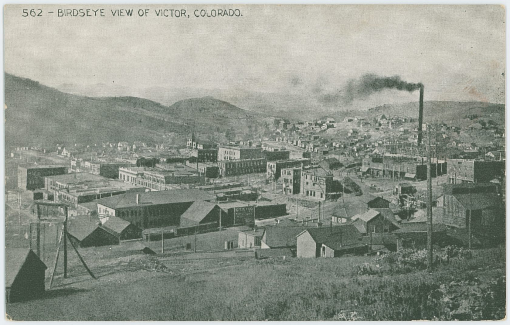 Yet another interesting view from Battle Mountain towards the Gold Coin mine in Victor, as it is getting rebuilt after the 1899 fire that destroyed the old mine and lot of the town itself. Just too bad that all edition of this view that I've seen is from printed sources, from the bad quality printed postcard this view is from, to an even worse in a Souvenir folding book published to promote the Midland Terminal. While it is really hard to tell, it appears possible that in this view not even the Ore-house has been rebuilt yet, but it is too darn hard to tell for sure. I see the smokestack, the head frame can be picked out as exposed, and it looks like there is a wooden frame around the area where brick walls are known to have been. It may also be in the time frame around 1920/1921 when they tore down the Gold Coin, I really can't tell from this single image! In the foreground, right, is the distinctive Ore-house of the Mary Cashen seen, and outside the view to the right would the head frame for that mine be.  Victor Public Sampler is the long structure just left of the Mary Cashen, with its cupola on the roof and with part of it outside the view at right. The mine seen with its small head frame and hoist house at lower left is for the moment a mystery to me at the time of this writing [19.02.2017].