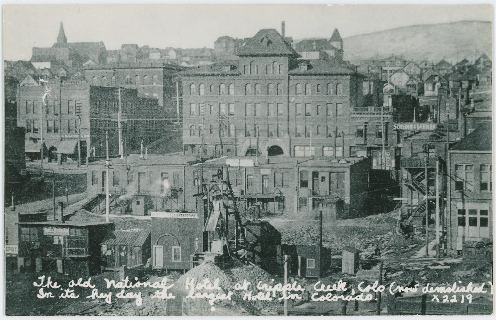 This view of Cripple Creek shows the Cripple Creek Enterprise Mining operation at the City Mine, or Cripple Creek City Mine, or other variations of similar names in foreground left, and the massive National Hotel more in center back. It also has a sign to the right of the hotel reading the name of two photographers Schedin & Lehman up on top front of a structure, which should be helpful in dating the image as there should be a way to learn when they did operate in the District, but I do not possess that info at time of this writing (30.03.2018).    Not the best quality but it is the only one I ever seen so Is hall not complain.
