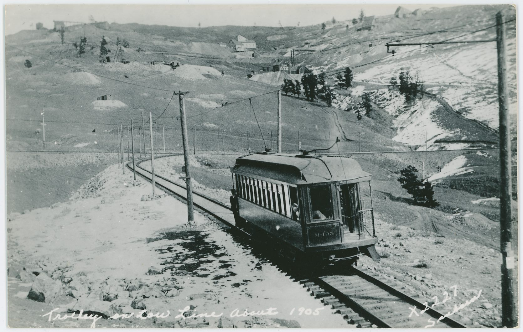 This view of Trolley No. M-105, heading for Cripple Creek on the Low Line, is taking just after passing Alamo Junction where there was a side spur for steam trains up to the Index mine ore house. At one time, there was a plan to extend the track up a siding along the Moon-Anchor mine, as far as I know this never happen though - only a road ever went there. Up near top of view, above the Trolley, is seen first the shaft house of the Rittenhouse Mine, then the Short Line grade climbing Gold Hill and then the shaft house and orehouse of the E. Porter-Gold King mine is seen with its cupola plainly poking up of the roof. Near upper left is seen a bad view of the Lexington Mine – easy to pick up due to the long trestle to the quite large ore house of that operation. A water-tank is seen left of that mine.