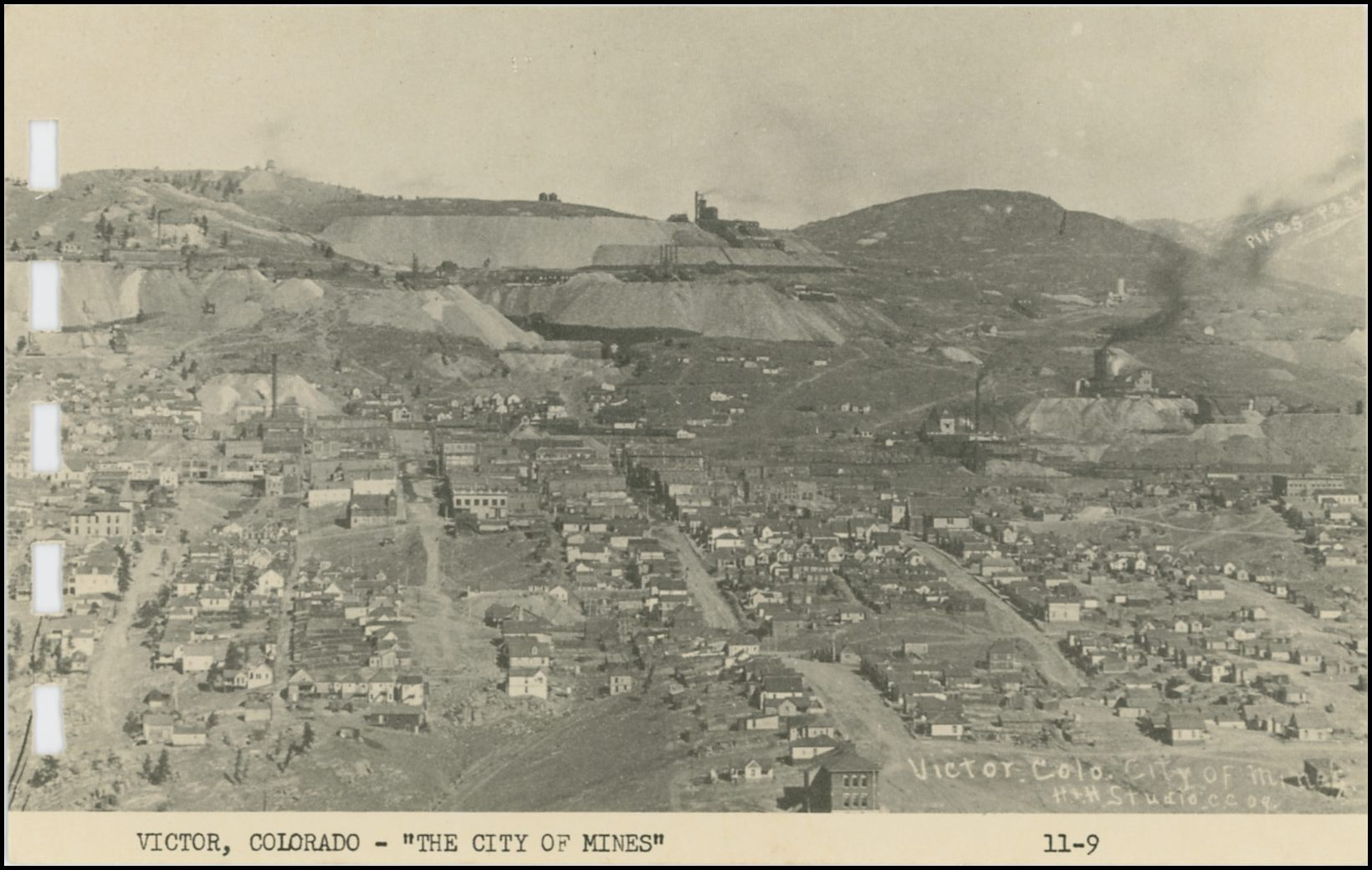 This view of Victor is looking north from Straub Mountain area. Photographed in 1909 by the H. & H. Studio in Cripple Creek, it was taken by either Hileman or Hill, impossible to tell for sure as the view is credited to them both. Being this is from a printed card in a small more modern postcard folder it is not the greatest quality, but one gets an idea of the town and the many mines in and around it. * Gold Coin, here marked as Granite Mine on the south facing ore-house, is seen about middle top/down and about 1/5 in from left-hand side. * Just behind the huge smokestack of the Gold Coin is the main shaft of the Dead Pine, named Oliver Shaft for some reason. The dump is much easier seen then the mine itself. * Straight up from the Gold Coin smokestack, in the distance; against the sky; sticking up from the hill, is the shaft-house of the American Eagle. * The Ajax Mine is about 1/4 down from top left, about 1/6 on from left-hand side. * Further to the right of the Ajax would been upper shaft of the Dead Pine, the Granite (original shaft/mine) – seen about 1/3 in from left-hand side – and the Burns (main) shaft of the Portland mines, with the Portland No. 2 seen just off to the right for the center of the upper quarter in this view. * Towards the right-hand side is seen the Strong Mine, about half top/down and 2/3 in from the left-hand side. * The Independence Mine is just right of the Strong mine, seen with its huge dumps and structures. * The Vindicator Mine, shaft 1, is seen above the Independence mine, about 1/3 down from top.