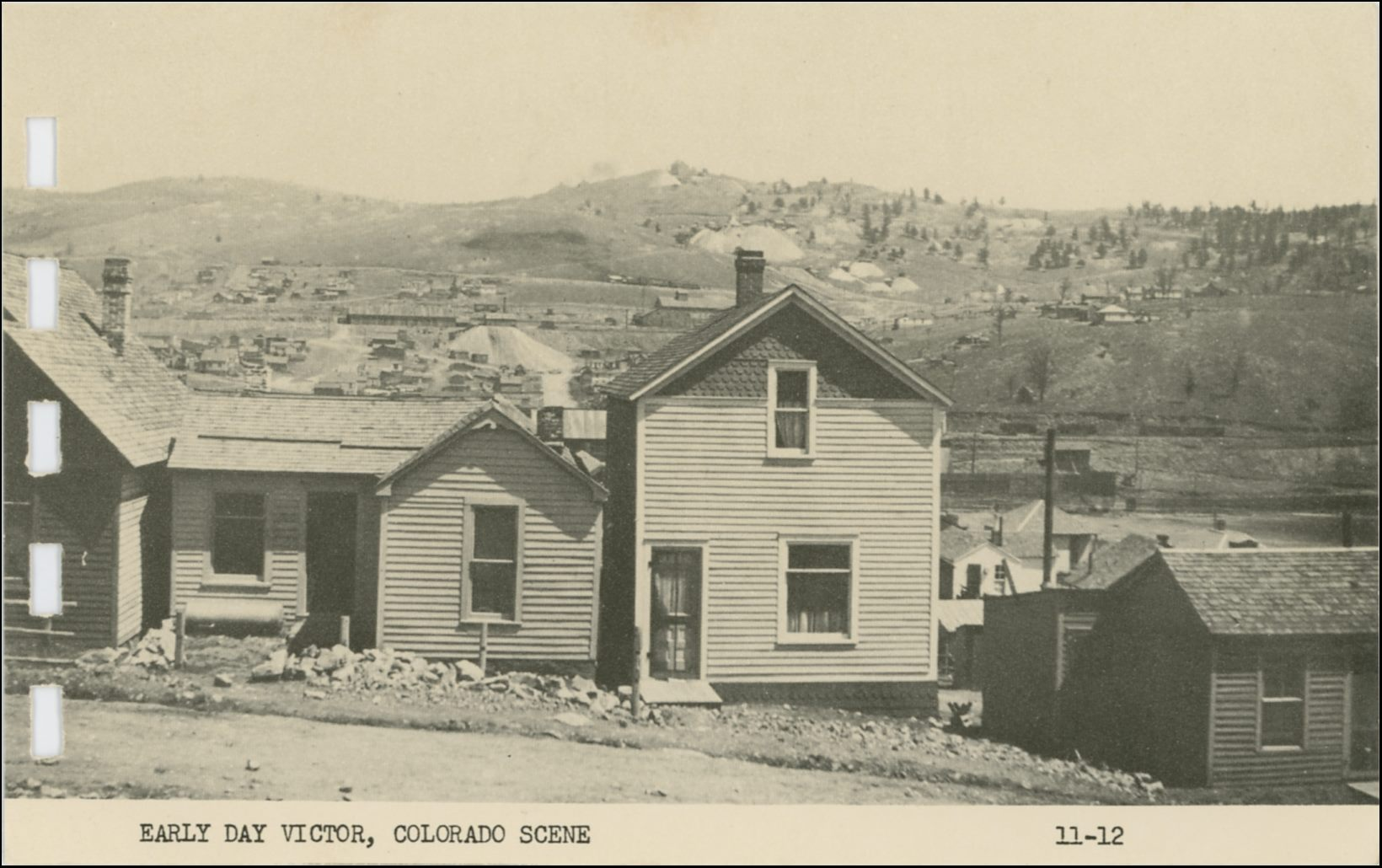 This view of Gold Hill from a street in southern Cripple Creek is mislabeled to be an early Victor scene for some unknown reason. Being this is from a printed card in a small more modern postcard folder it is not the greatest quality, but one gets an idea of the area it pictured. I've been unable to pinpoint the street in the foreground, but I think it might be the First Street, possible south Colorado Ave., but I doubt it as this don't look that far up the hill. * Either way, about center left/right and 1/3 down from top, behind the two-story house in foreground, on get to see the north half of the Cripple Creek Sampler, located up along the M.T. roadbed, with the Short Line railroad below it, having come around the hill at right hand side. Incidentally, the original locating of the sampler was along the F. & C.C. grade seen just below the top/down center on the right-hand side, and would have been hidden by the same two-story house. * About 1/3 down from top, and 1/3 from left-hand side, a long structure will be seen, that is the Trolley Barn for the High/Low Lines of the Electric System of the Short Line railroad. The big dump just right of the Trolley barn I think is part of the Cripple Creek & Gold Hill Deep Mining & Development Company operations. * Straight up from the chimney on the before mention 2-story house there is a big dump that I think is part of the Midget operations. * About center left/right and not fully 1/6 down from top, above the before mention Midget, is the characteristic shape of the large Shaft-House of the Anchoria-Leland mine seen against the sky at top of Gold Hill.