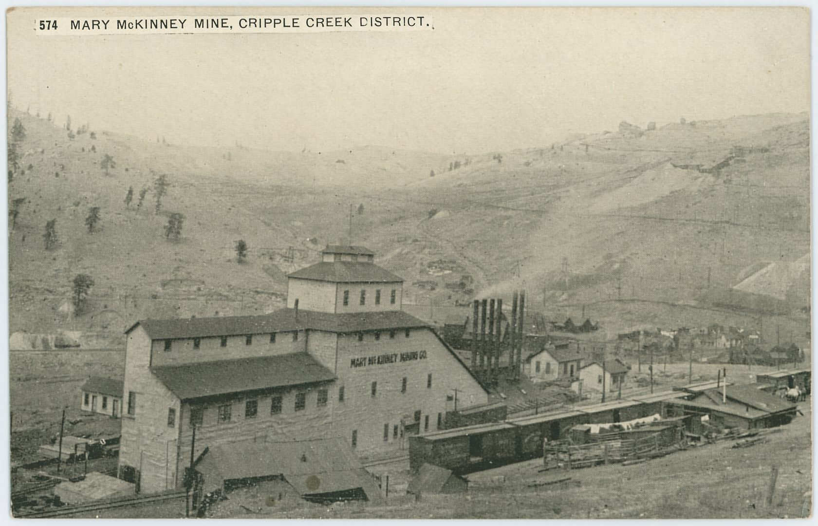 I've seen this image used three times, for this card and another postcard where there are a couple of extra millimeters visible on the right-hand side, plus I've seen it used in a postcard folder.    The view is from the railroad side of the Mary McKinney mine, showing several box cars parked on sidings nearby and at the mine itself. It also shows part of Anaconda at right-hand side about 1/3 up from bottom, the part that survived the 1904 fire, as I see no signs of structures at left side of image, and I believe there should been visible something there if the town was still there.    The tracks in the foreground belong to the Midland Terminal, but the Mary McKinney mine was once served by dual gauge as the F. & C.C was also having a spur to the mine, entering in from left-hand side, running parallel with the Shaft House to serve that and the coal bins at the power plant seen with all those smokestacks to the right of the shaft-house.    Behind the smokestacks of the Power House of the Mary McKinney you can see the Ore House of the Anaconda Mine, located down by the F. & C.C. yard in Anaconda, but image is too bad to really make out any details. Which is sad, as up on Gold Hill seen in the background, there is seen the Shaft House of the Anchoria-Leland about 1/4 in from right-hand side and about same from top, with the Ore-House and trestle of the Lexington Mine seen just to the right of the Anchoria-Leland.    Or even more sad, there is visible a mill on the hill side above the Low Line grade, seen about  1/3 down from top and 1/7 in from right-hand side, a mill I believe might be known as Anaconda Mill, but I might be mistaken where that mill was located as info been a little scarce, but it fit the location of west slope Gold Hill.