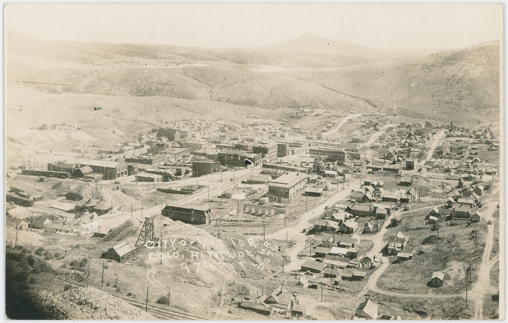 This view of Victor from Battle Mountain up near the Ajax mine is possible from the 1930's, I am not sure, as there are no dates to go from. The postcard has a EKC stamp box on the backside, and Google gives info that this is from the 1939-1950 timespan, so late 1930's might be a safe bet. There are still rails seen, with railroad cars, so I would guess the M.T. is still running, making this also fit the late 1930's and very early 1940's timeframe. In foreground towards lower left is the head frame and hoist house of the Oliver Shaft of the Dead Pine mine seen, with its big dump stretching out towards the town and the rails of the M.T., which depot can be seen left of the head frame. An exposed more modern version of the Gold Coin head frame can be seen about middle top/down and about 1/3 in from the right-hand side of the card, with the ruins of the brick walls seen around it, check out the image in the Gold Coin base image view, as number 7. In a sort of continued line from the head frame of the Dead Pine through the Gold Coin, one can see the dump area of the St. Patrick mine about 2/7 in from right-hand side and about 2/5 from top. Best seen as a cropped version of a higher resolution scan of this card, check out view 7 in the St. Patrick Base page image view.