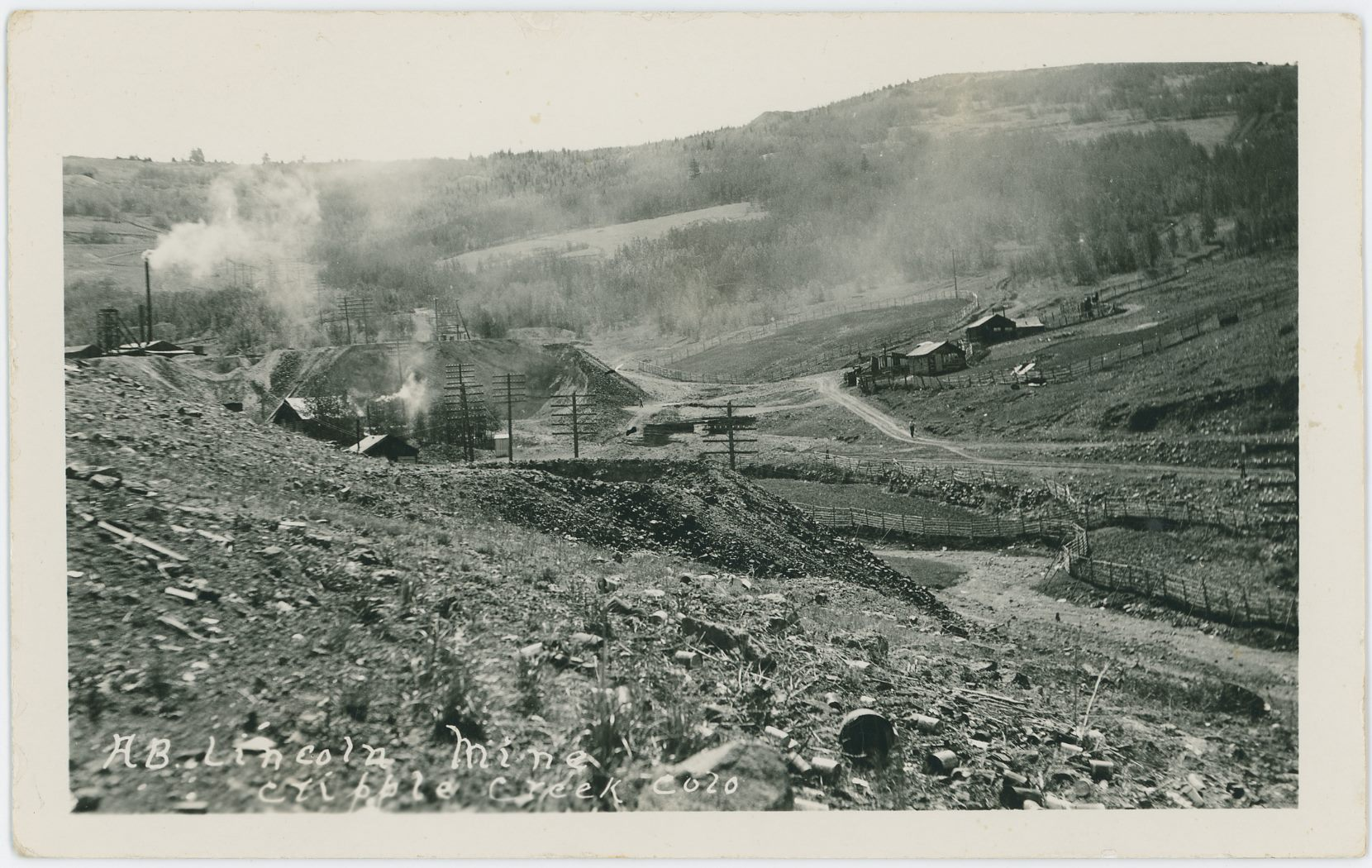 While this card is not marked, the Text Title has same type of writing as another card with the Young name on it, so I assume it is taken by the photographer named Young. The Scene is in lower Poverty Gulch, looking towards Gold Hill in the background, with the large dump and operations of the Abe Lincoln Mine seen at the edge of the left-hand side, going into the image towards right. The Dump with a hole in the foreground I can't say at this moment in time [13.06.2017] which claim it was located on, so sorry I can't help with that. What I can say is that I assume this view to be in the 1930's or so, and there are seen two switch-stands about middle top/down on the right-half-part of this view, where I think the one closest to the right-hand edge is the one for a siding at the M.T. Wye below the old Midland Sampler site, while the one to the left is the one for the upper spur that went to the top side of the same Sampler. There also appears to have possible been a loading dock of woods at the end of the spur near the end of the mine dumps of the Abe Lincoln.