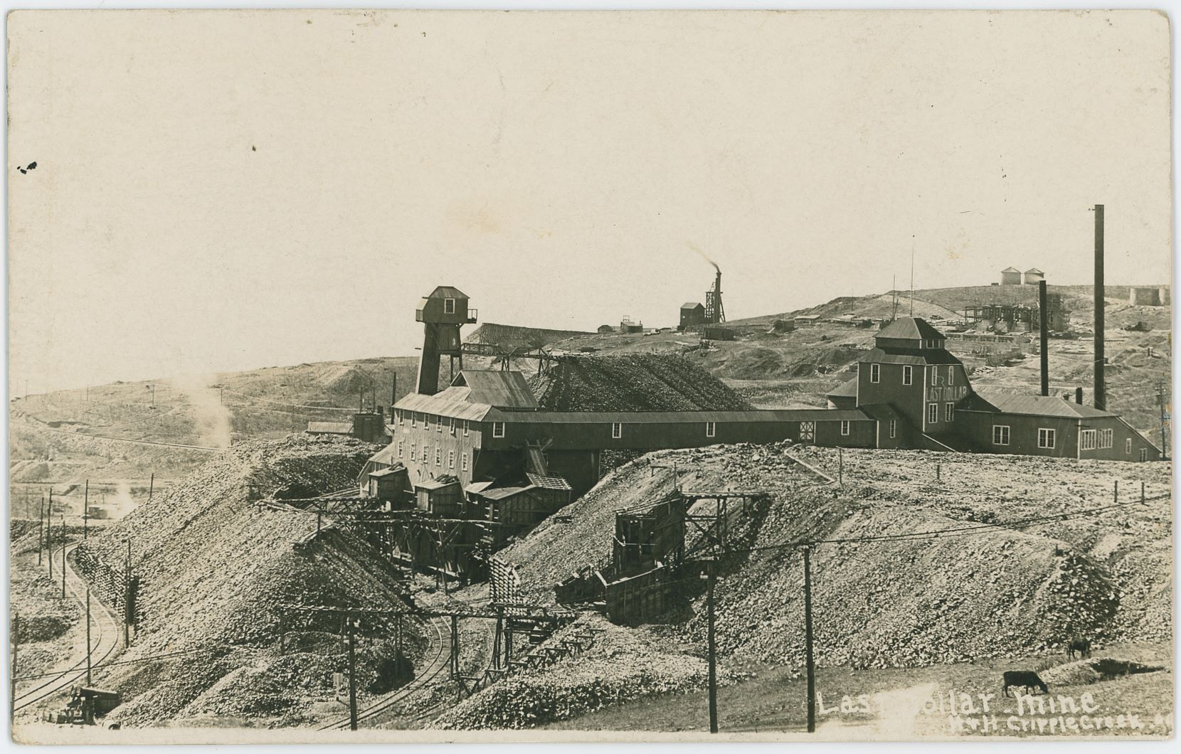 This is the second version of this card I've seen, different crop where there is a little more seen at the bottom and on the left-hand side, in terms of a millimeter or three. Marked as H & H, Cripple Creek, 09 – making this a view by either Hileman or Hill as they worked together at this time. I've also seen a version of this view where the left upper side has some hill visible, but both my cards have that missing in the faded distance.    I think the background right is showing part of what was to become Portland Mill on top of Battle Mountain, while the head frame and high tower like structure in background against the sky just right of the center left/right is from what I'm able to gather, the Portland No. 2 Shaft & headframe, as it looks very much like some other views I have of it. I felt it was too visible from this angle, but I've been unsuccessful to find any other mine in that area to fit, so it must be the Portland No. 2 shaft.    The railroad track in lower left is the Short Line/High Line roadbed going towards town of Independence and the route down passed Goldfield and into Victor, while the railroad tracks seen nearly buried in the dumps at the Last Dollar mine is the side-spur of the Golden Circle 3-foot track going towards the Vindicator Mines and for a short while the Black Sampler at Victor Pass.