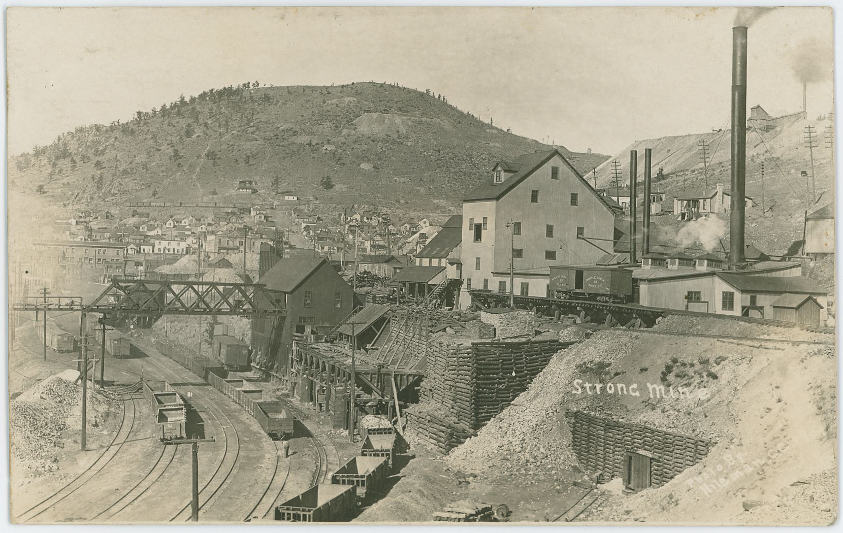 This view of the Strong Mine is quite a good one to tell how it looked sometime in 1909 when T.J. Hileman took the photo which was the base for this postcard view presented here. Down left is the yard of the F. & C.C. railroad, while the mainline of the Victor branch of the M.T. is shown entering the scene along the right-hand side, where there is also a side-spur for delivering coal to the powerplant of the Strong Mine for their operations, seen here with a single M.T, boxcar (no. 211) parked on the trestle, while the mainline where passenger trains was running is this side of that trestle, dropping downgrade to reach the Depot not seen in this view due to be behind the Strong Mine Ore-house.    Just behind the before mention ore-house is the Ore-house and headframe of the Mary Cashen Mine seen, with dumps around it and some of their cribbing's is seen behind the big truss bridge coming out of the Strong Mine Ore-House, extending across the F. & C.C. yard unto another smaller bridge and taking it to a rock-house outside this view which delivered dump ore to Short Line cars to be used as ballast, fill-mass and similar along the lines, from what I have understood it as.    Up near right top corner the dumps and Shaft House of the Ajax Mine is seen poking up into the sky, and about center left-right and about 1/5 down from top, there is the dump of the Nellie V. Mine with a smaller two-post Head Frame and a hoist house and shed together as a long structure from what I can gather in a high dpi scan of this view. This do not match what Sanborn 1908 say the Nellie V. mine was to look like, as that say it is a shaft house type of structure.    I wonder if I see the Columbine Tunnel or if it is another one which is seen a distance to the left of the extension of Diamond Avenue up to the M.T. tracks in the higher dpi scans. Seen about 1/5 in from the left-hand side and 2/5 down from the top, a dump is there in addition to a tunnel portal and some sheds to the left of the adit opening.