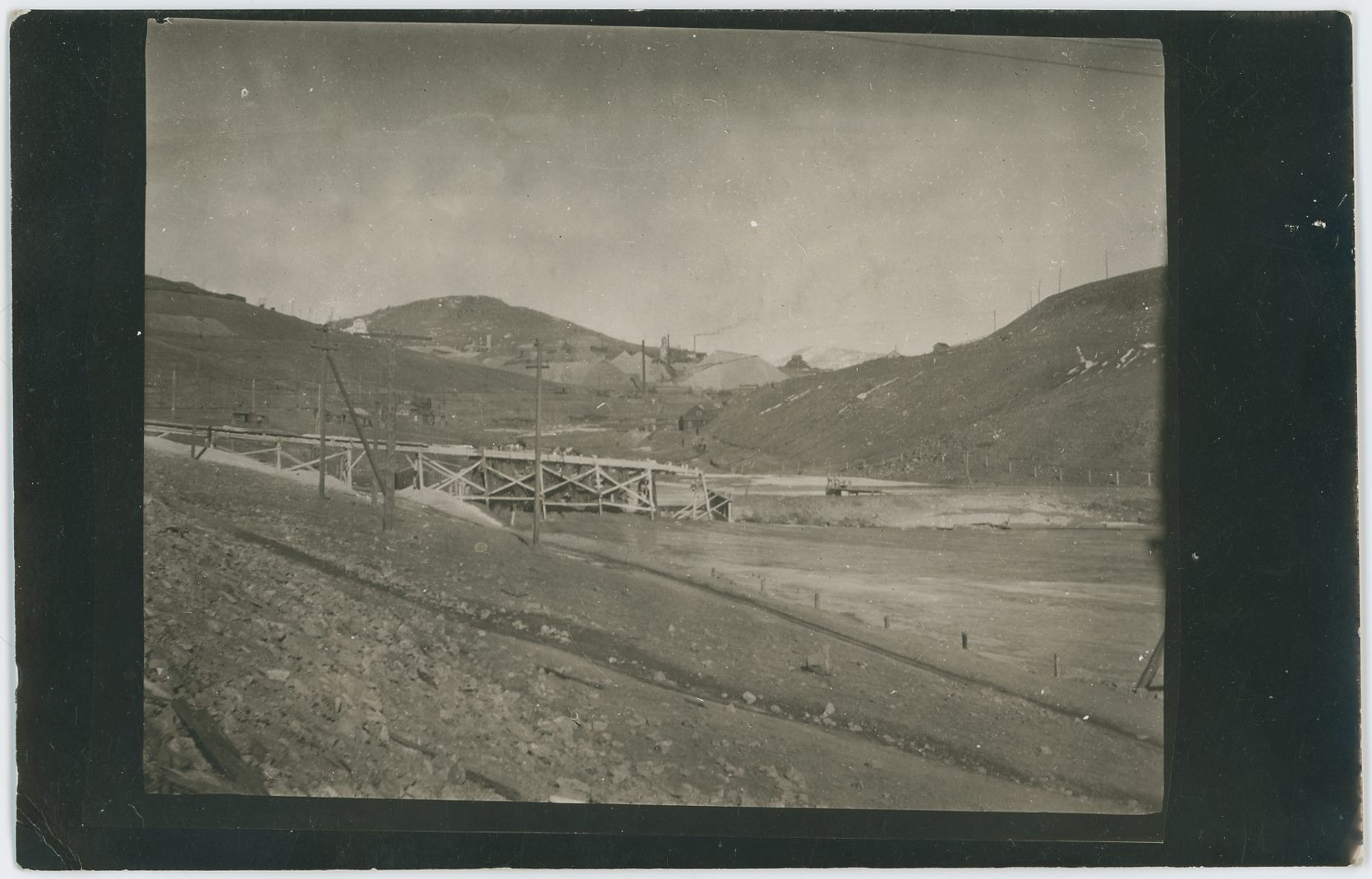 Sadly, not the best quality view, blurred, possible due to the copy nature of this view? The view itself is from the Slime Dam below/east of the Independence Mill, possible by time this view was made, also known as the Portland-Independence Mill – can't tell for sure as I have no date on this view. It is looking up the valley where Wilson Creek ran, Bull Hill/Cliffs in distant background.    * The covered Head-Frame of the Vindicator No. 1 Mine appears to be visible about center sideways and about 2/5 down from the top.    * Smokestack of the La Bella Powerplant Structure is also seen, just left and below of the before mentioned Vindicator.    * The Black Sampler, or Cripple Creek Sampler upon Victor Pass is seen about 2/5 down from the top and about 3/7 in from the right-hand side.    * The Eagle Sampler is seen also about 2/5 down from the top and about 1/4 in from left-hand side, seen as a whitish structure against the background hill.