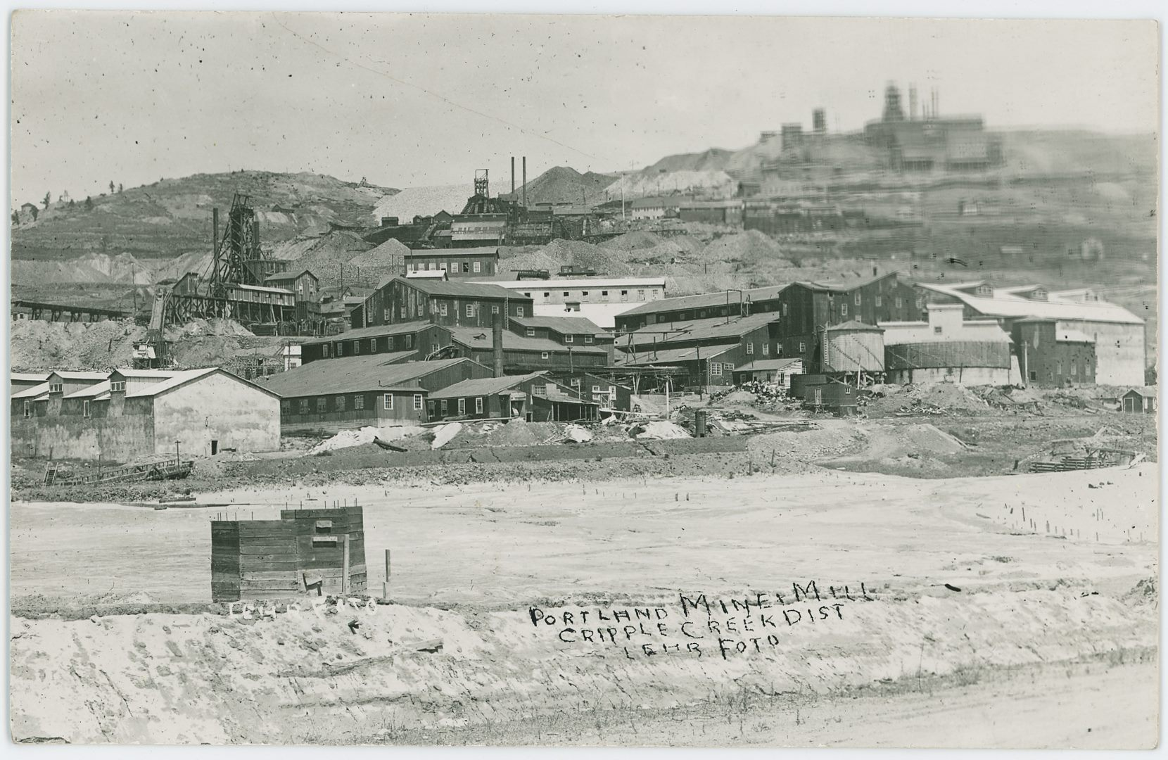 A view at the cramped hillside below the Independence Mine, and the Portland Mines, as the space been used for making quite a large mill, with what appears to be a slime dam in the foreground. Seems like this has obliviated the roadbed of both the Golden Circle and the Short Line/High Line railroad beds, but maybe not fully, hard to tell for sure.    Sadly though, the Portland No. 2 Mine, up in upper right top is way out of focus and not useful at all except for location purposes as the shape of it can be seen between the very blurred view in that area of this postcard view. The Independence Mine has lost its Shaft House and has an open Head-Frame, so that might help date this image, same as with the large mill in the foreground, by time of this image being photographed this mill has been bought by the Portland Company, even though it originally was part of the Independence Operations.